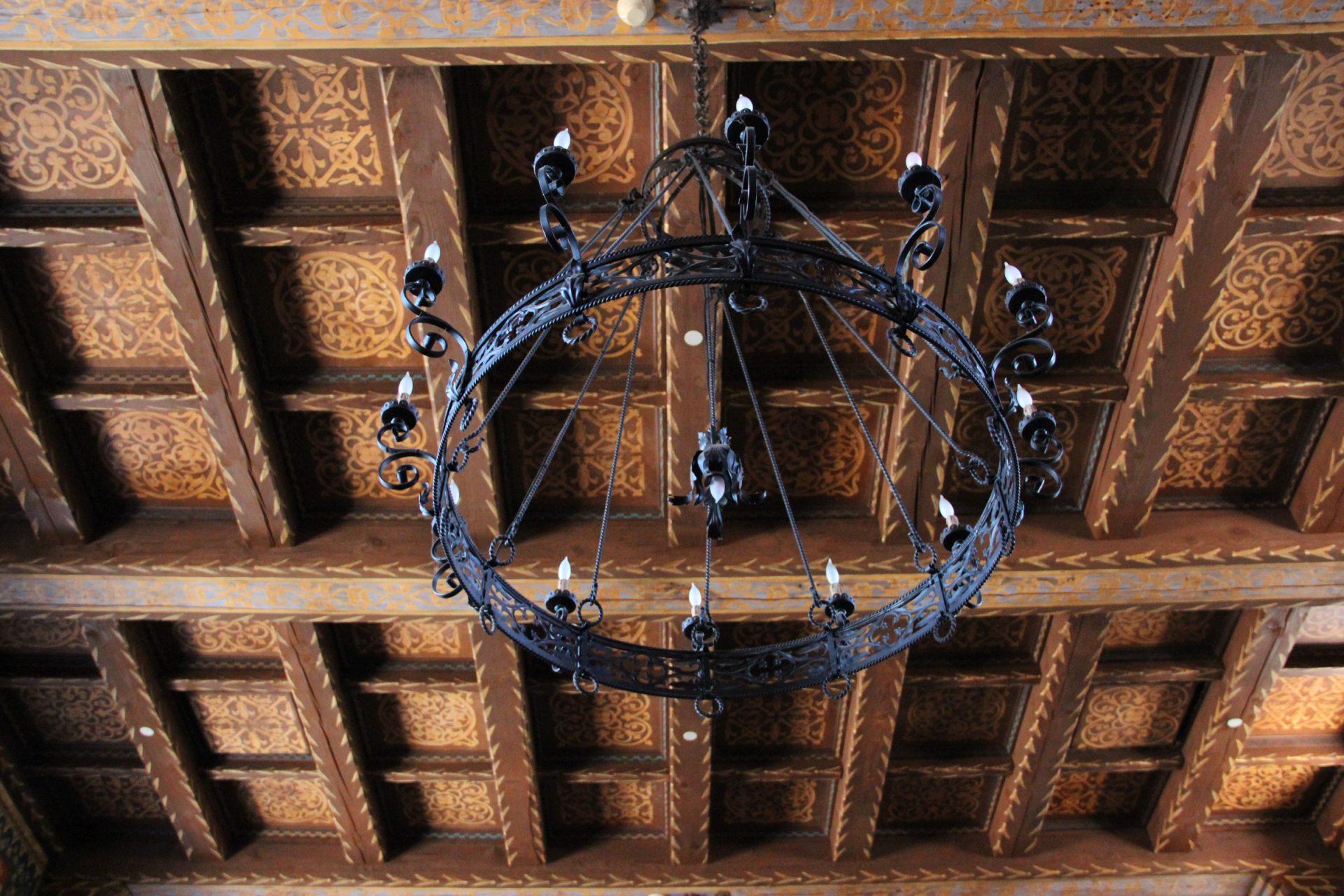 Black Metal Chandelier On Wood Ceiling