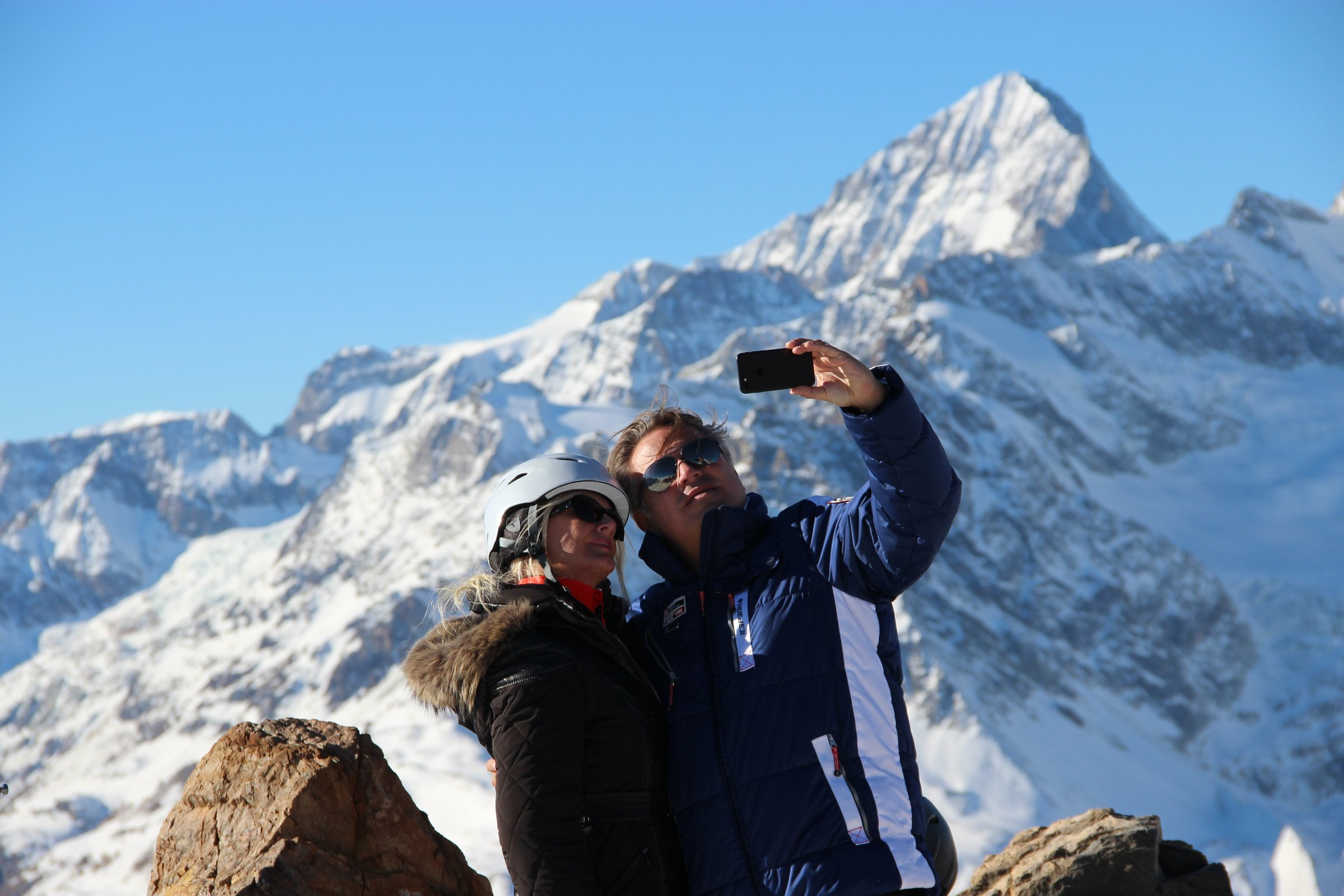 Couple Taking Selfie in Front of Snow-Covered Mountains