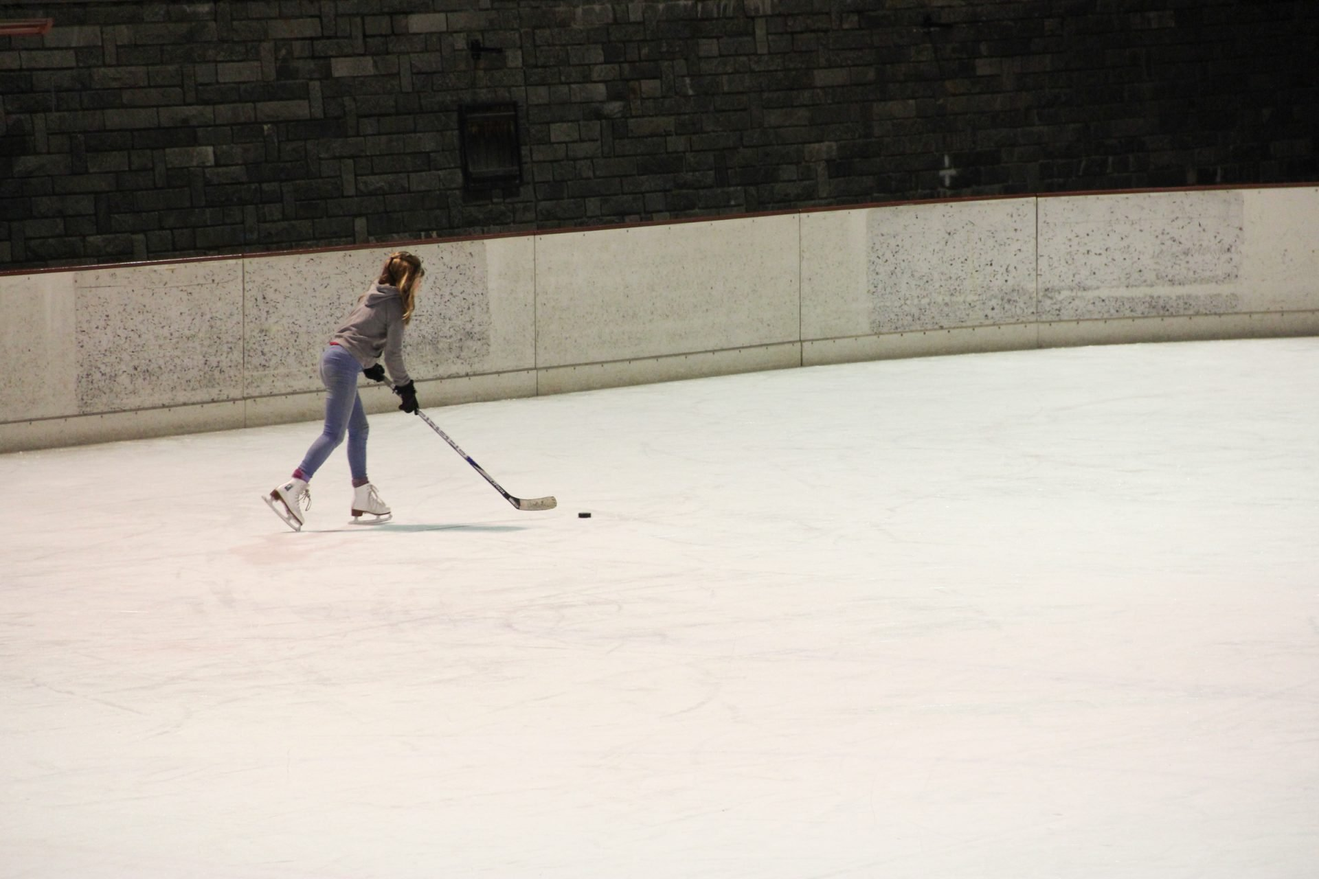 Girl Skating on Ice with Hockey Stick