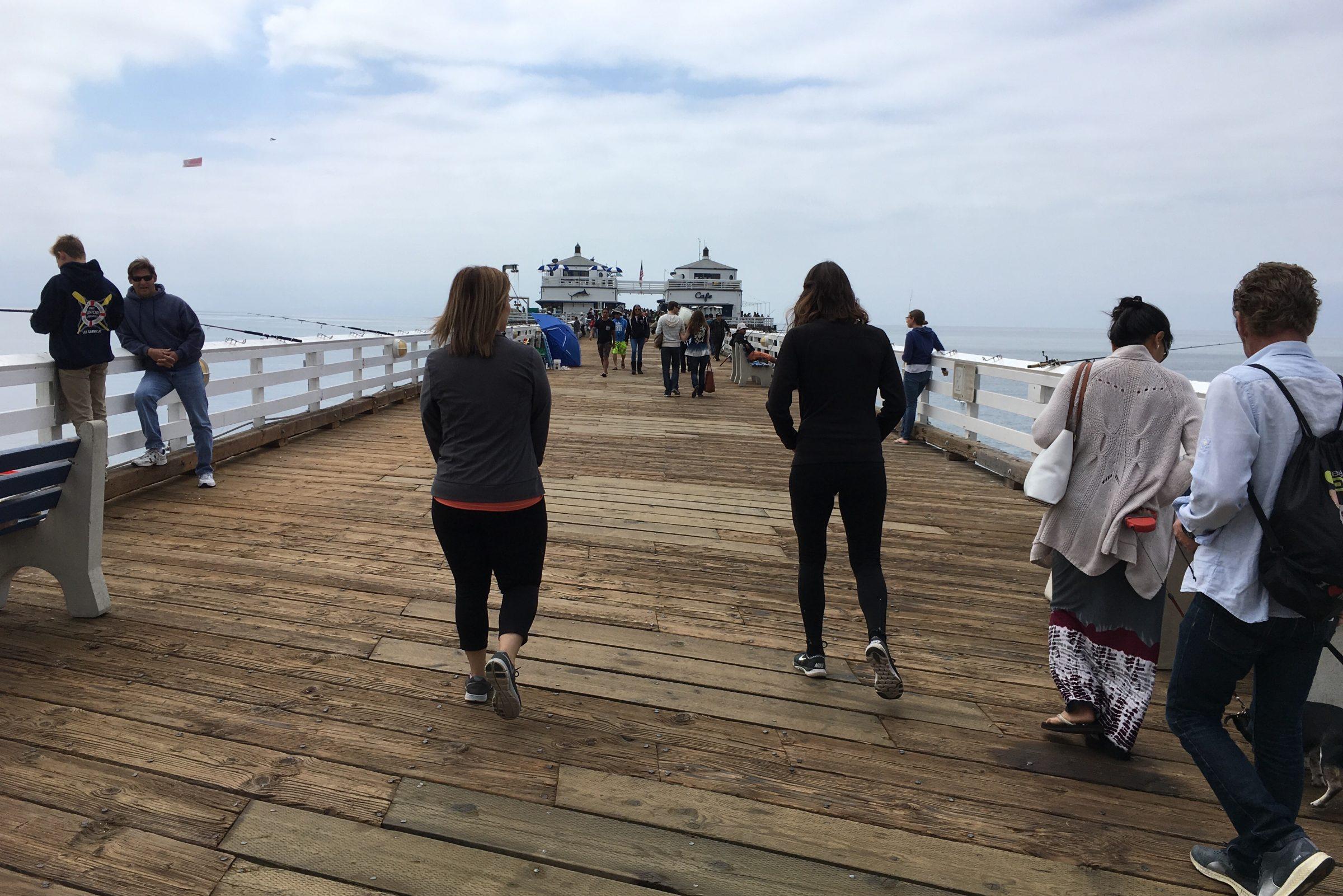 People Walking on Wooden Pier at Ocean