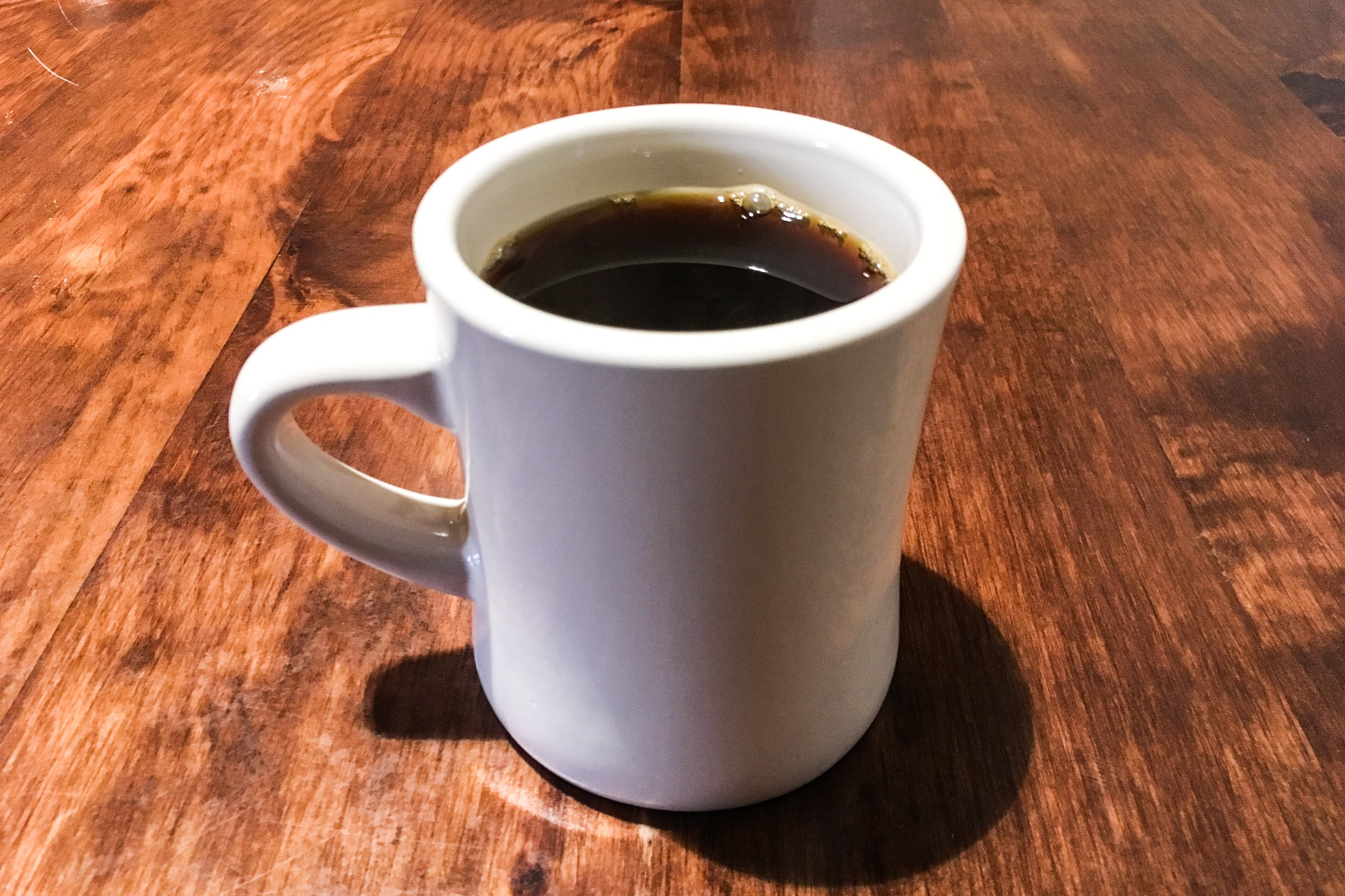 White Mug of Coffee on Wood Table