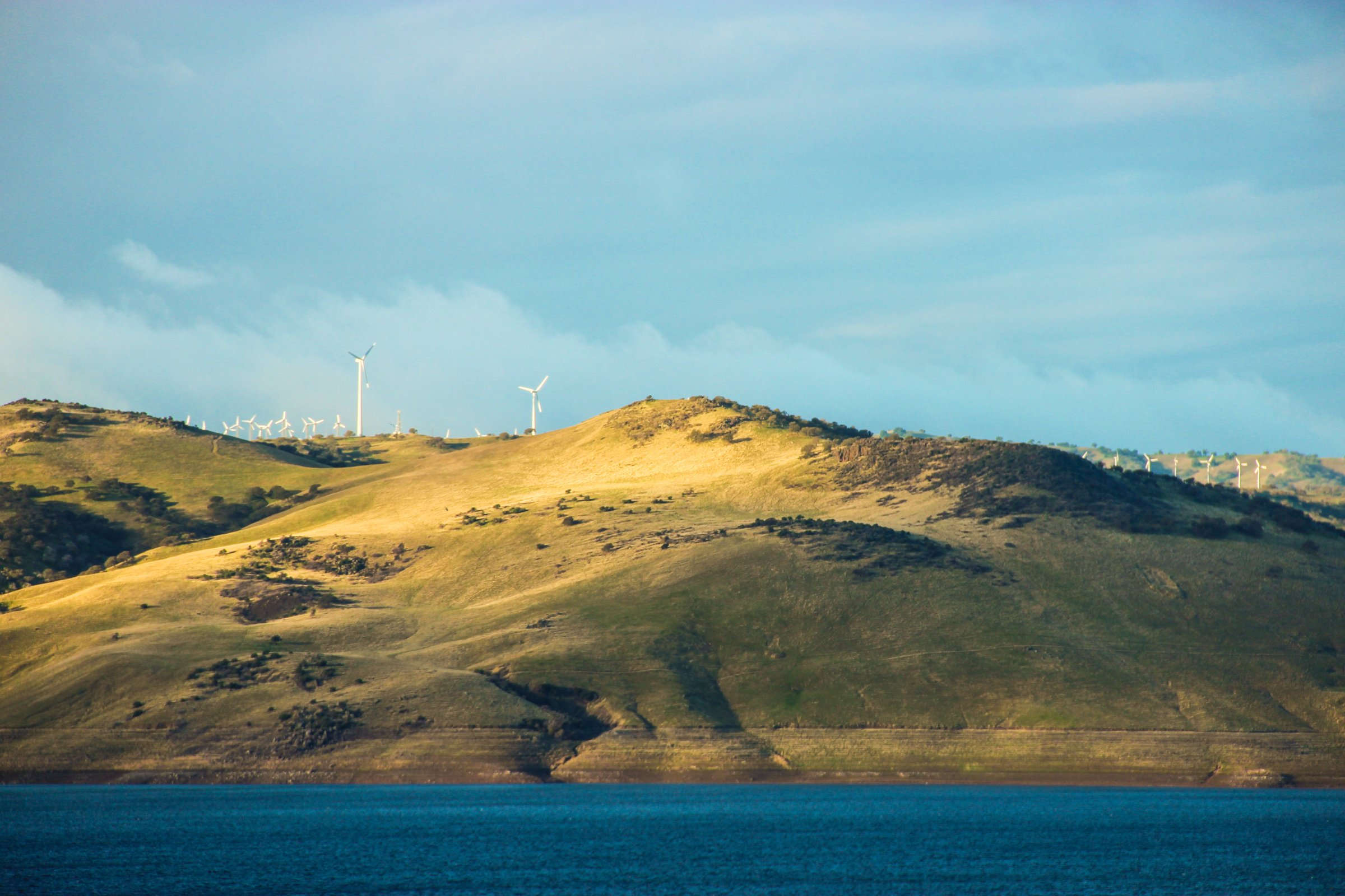 Wind Turbines on Hill Next to Lake