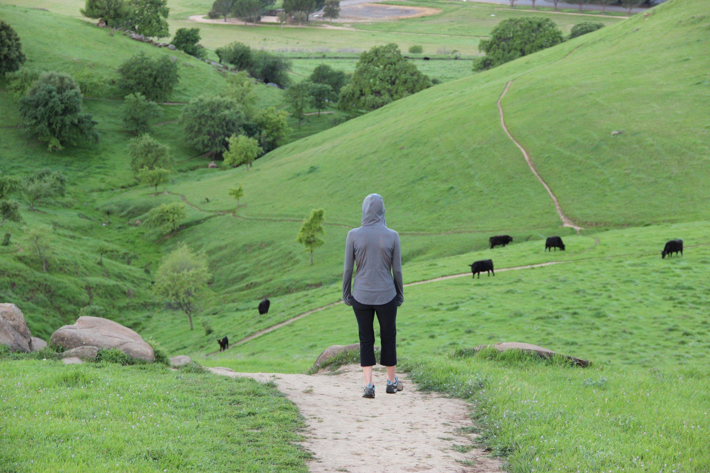 Woman Walking on Path Through Hills
