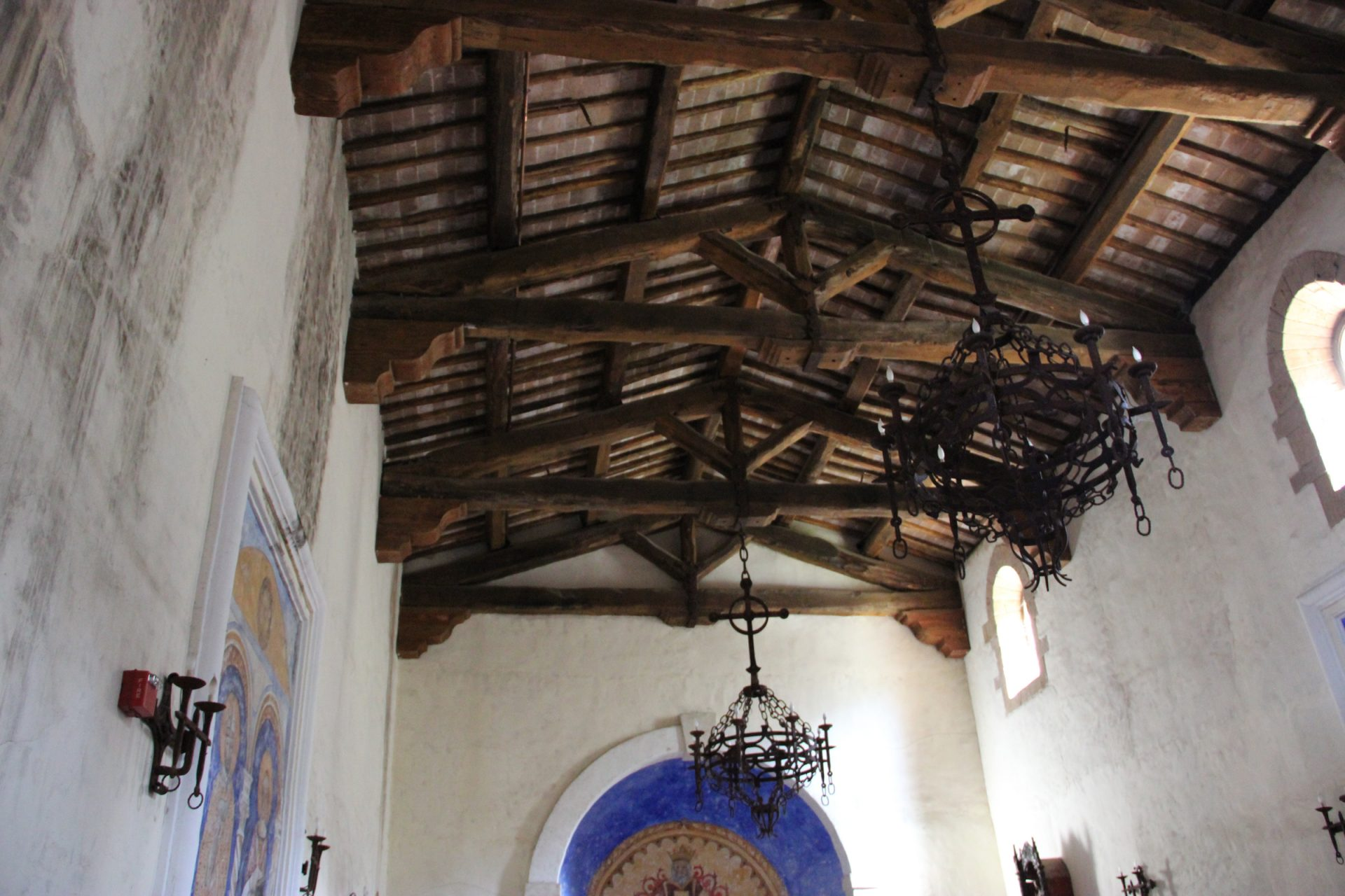 Chandeliers Hanging from Rafters of Old Church