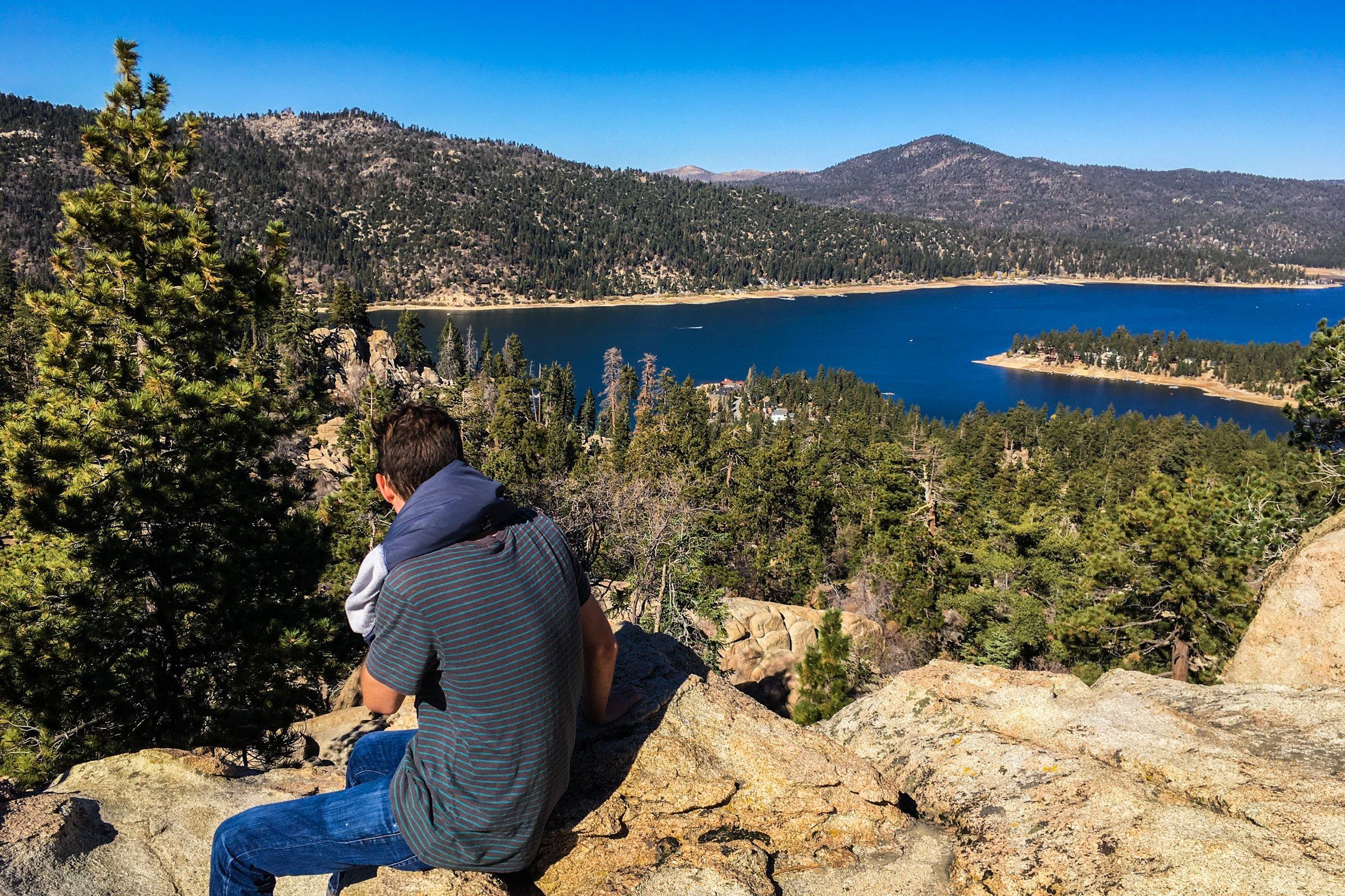Man Sitting on Rocks Gazing at Lake