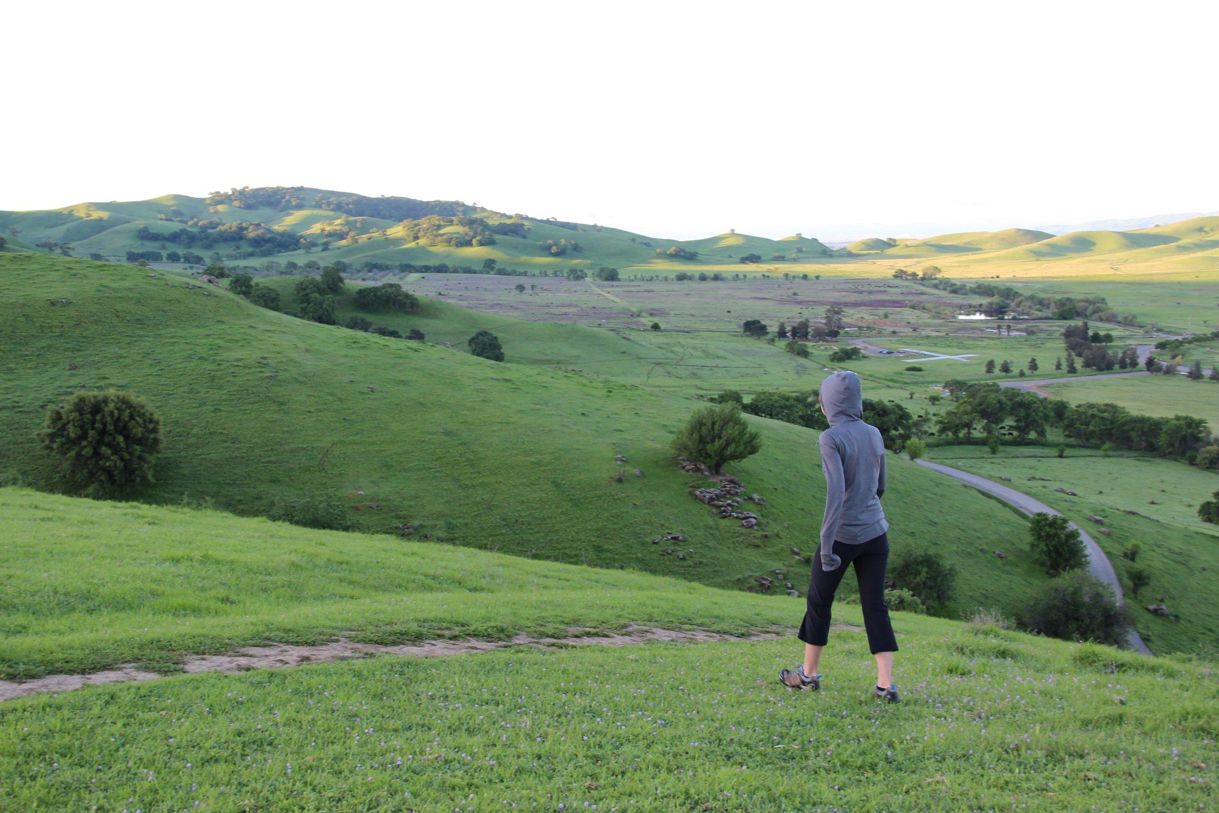 Woman in Grey Hoodie Walking on Hills
