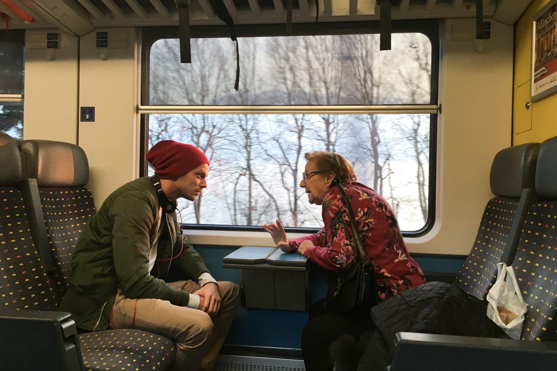 Young Man & Old Woman Talking on Train