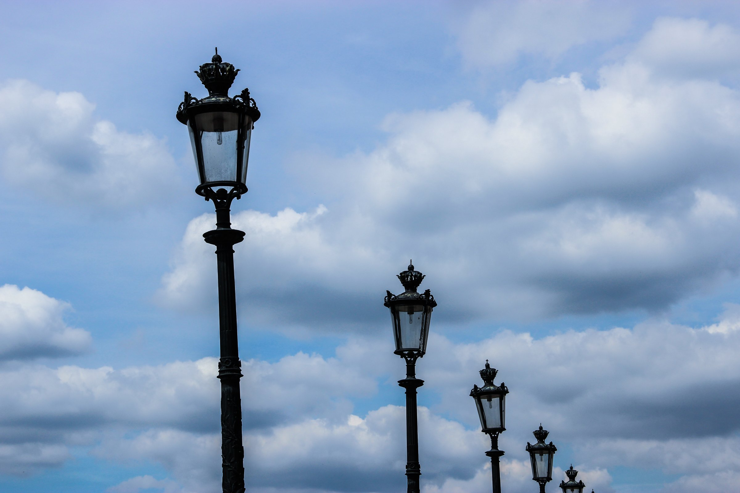 Lamp Posts Under Sky With Clouds