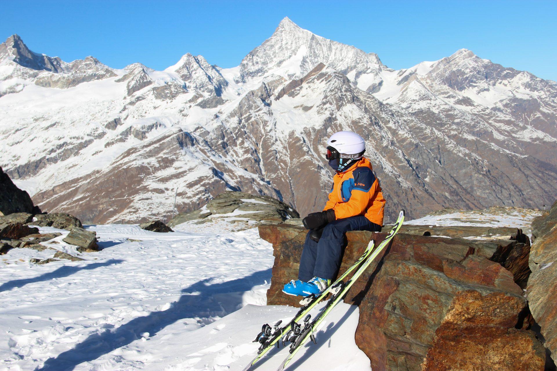 Boy Sitting Next to Skis in Mountains