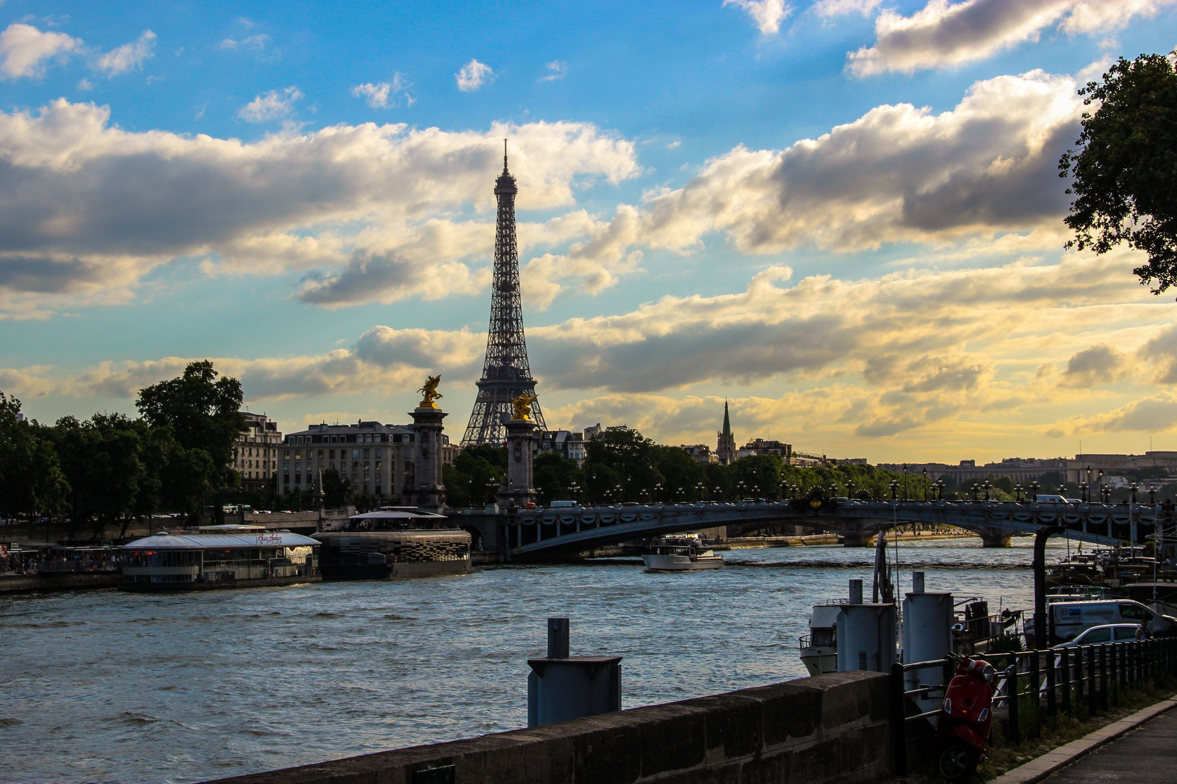 Eiffel Tower by River Under Clouds