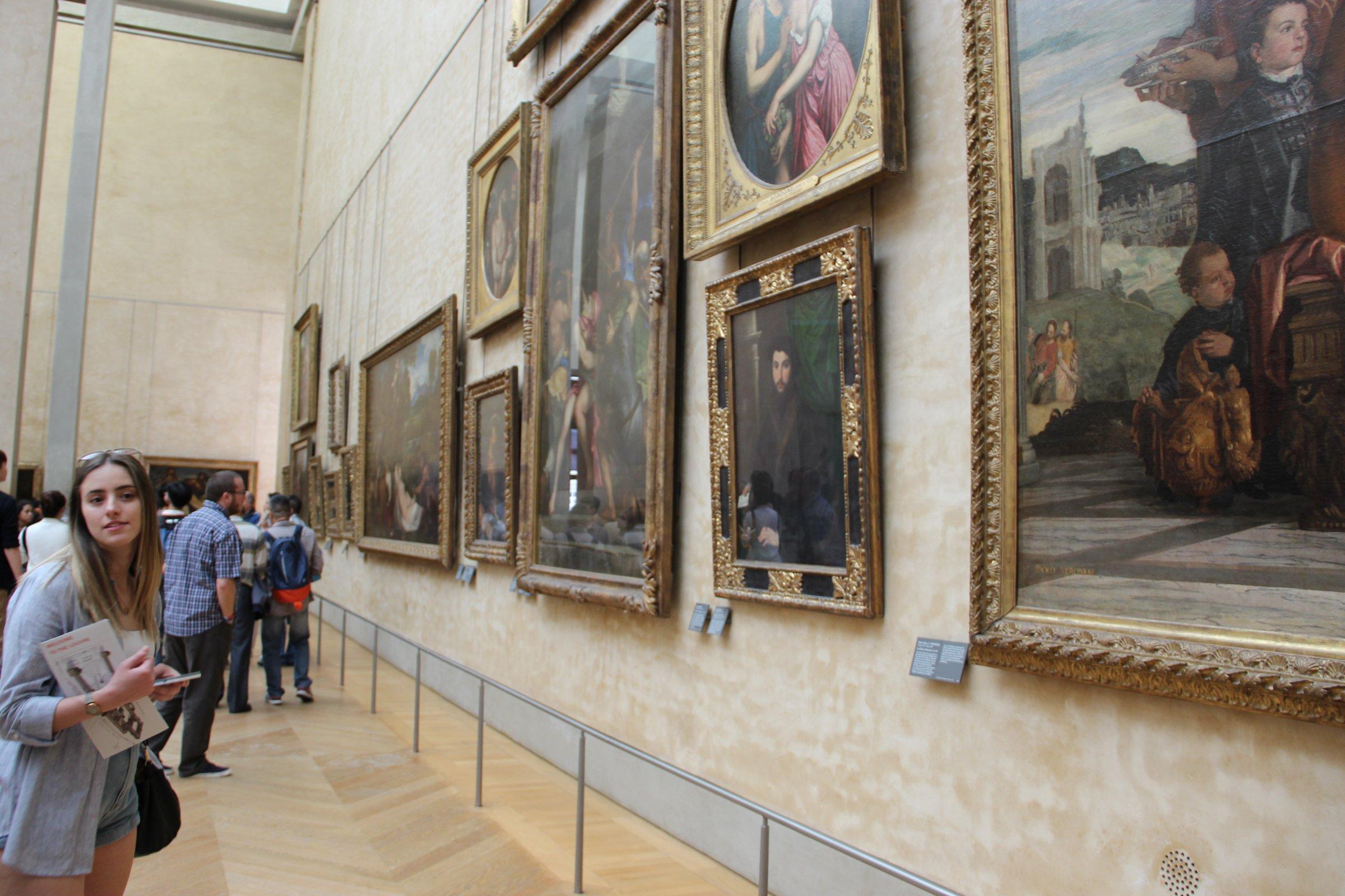 People Looking at Paintings in Museum