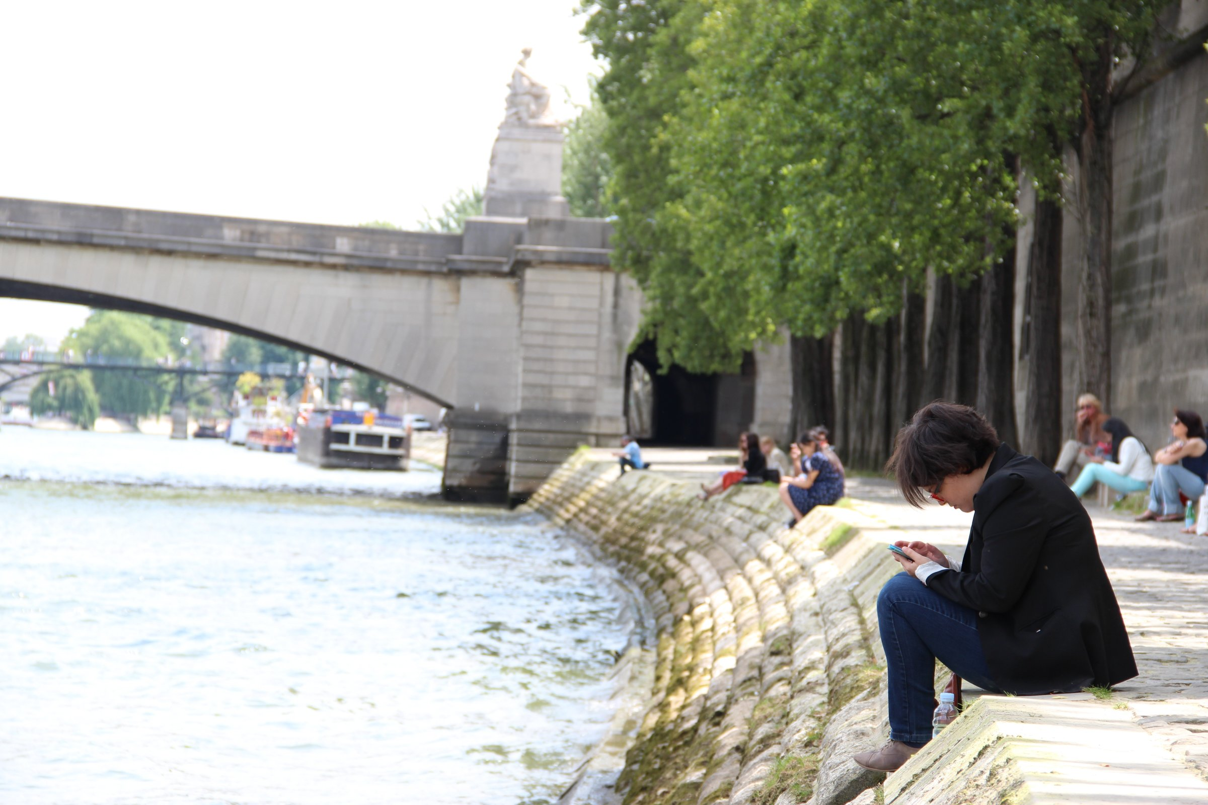 Man on Phone Sitting by River Bank