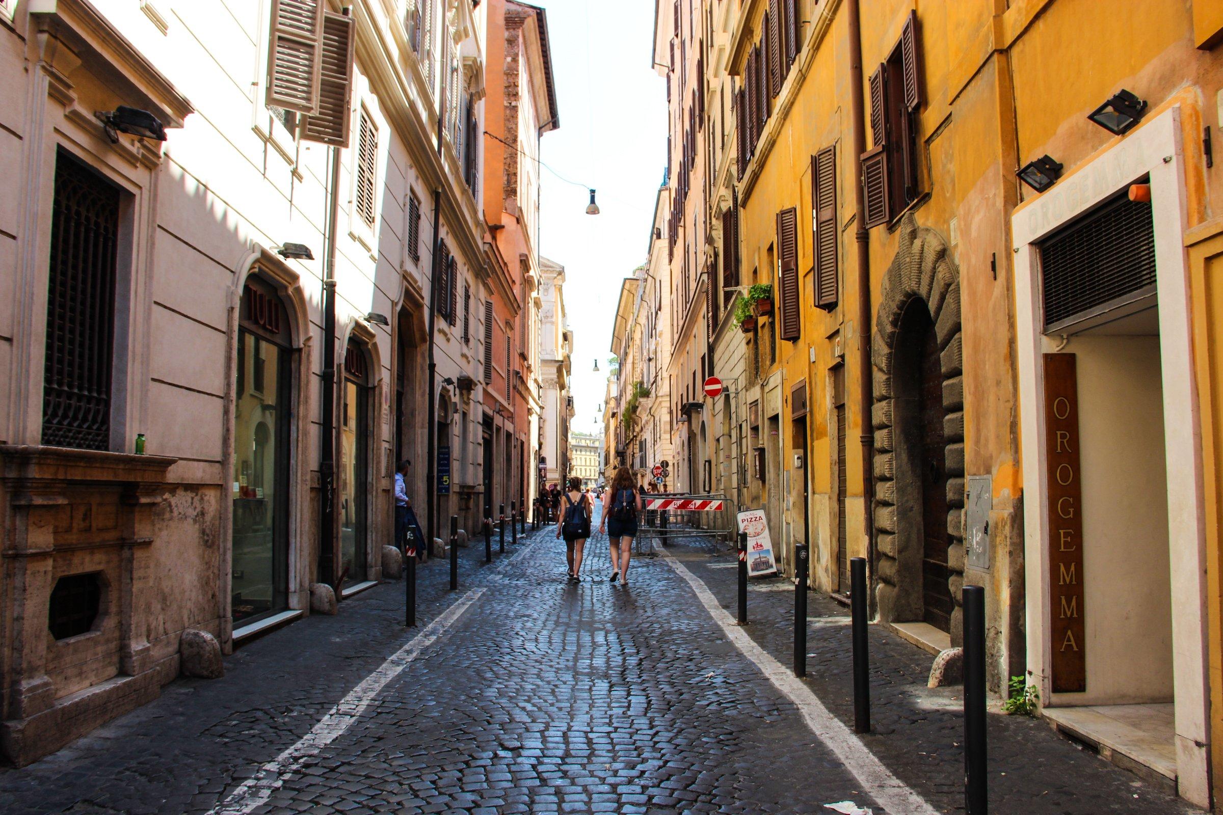 2 Women Walking Down Street Alley