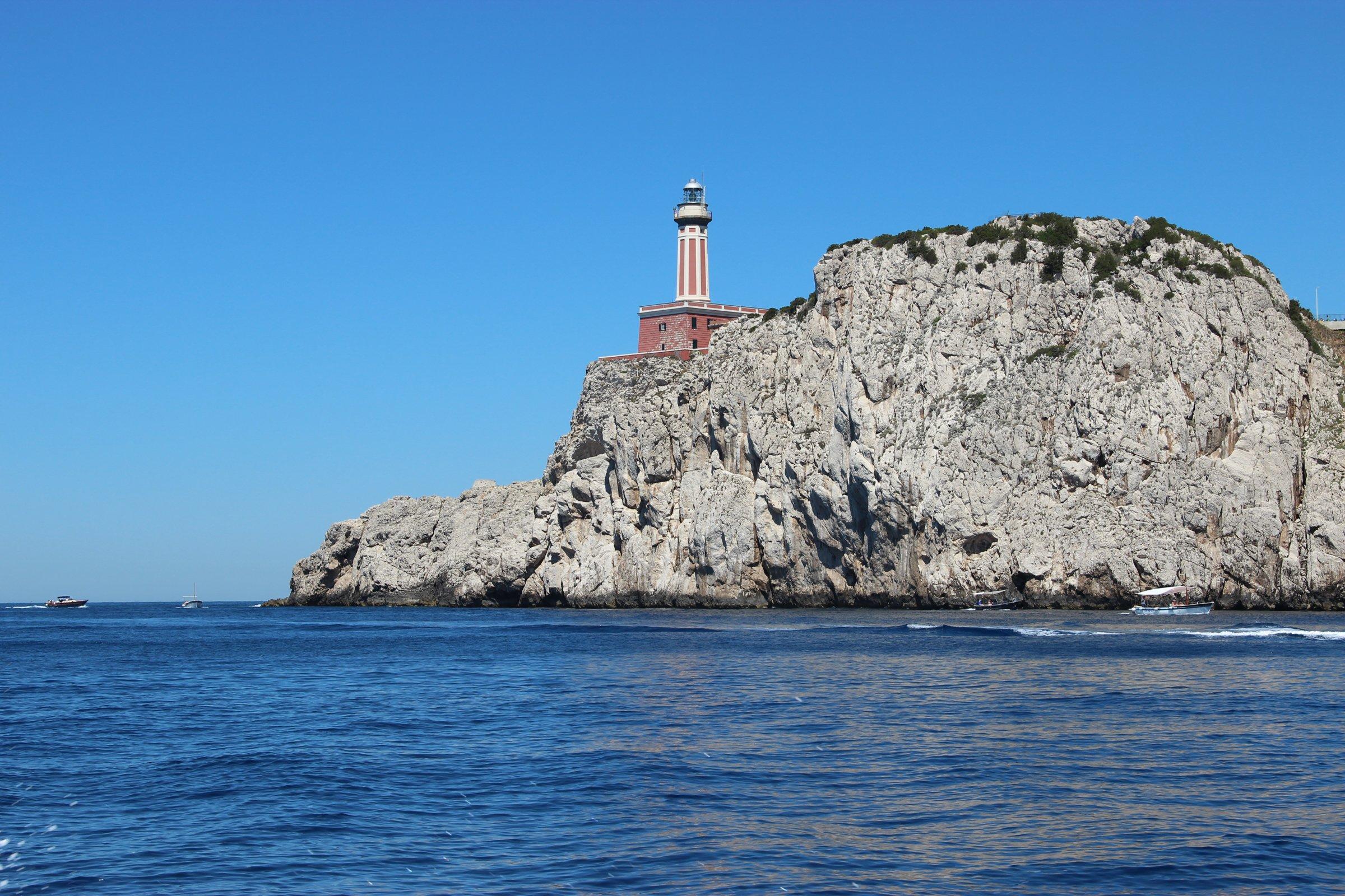 Lighthouse On Rocky Cliffside In Ocean