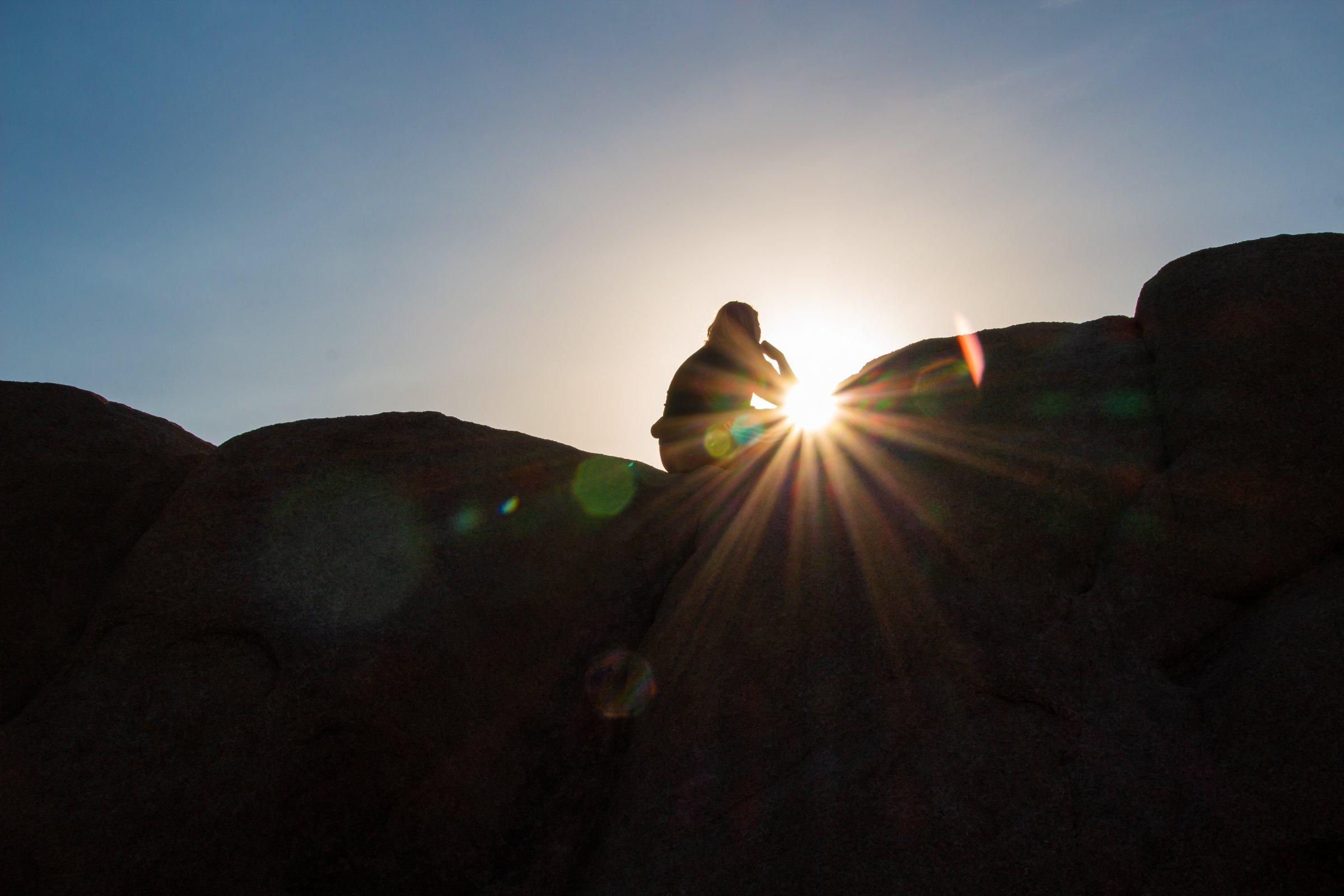 Woman Sitting On Rocks