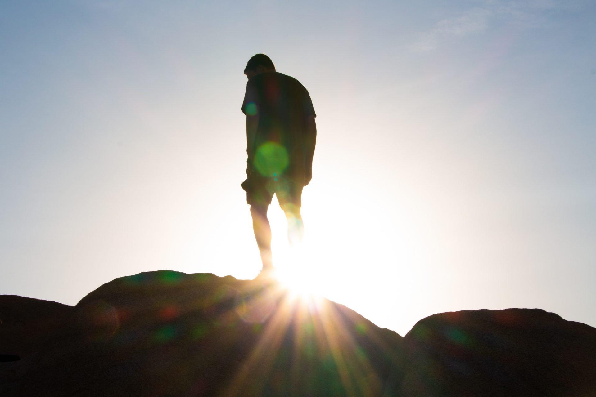 Sunrays Through Man Legs On Rock
