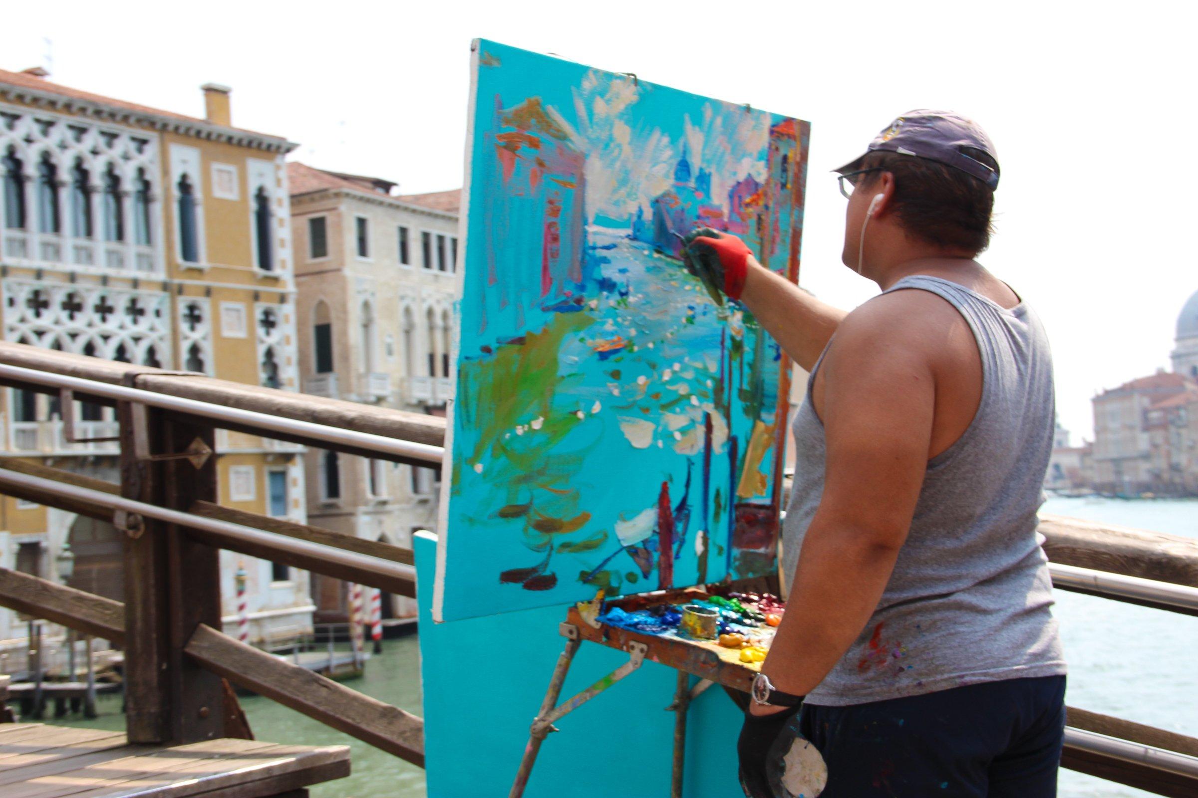 Artist Painting On Bridge Above River