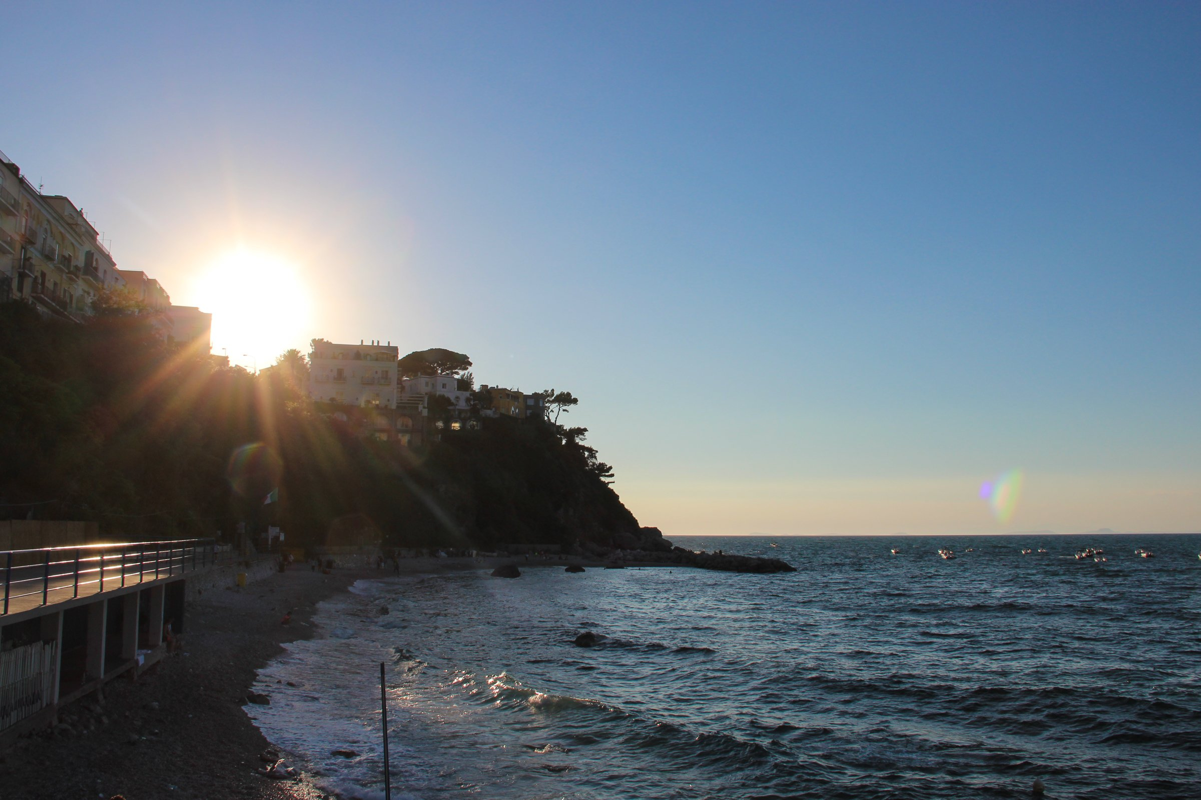 Sun Rays Through Buildings On Cliff Near Shore