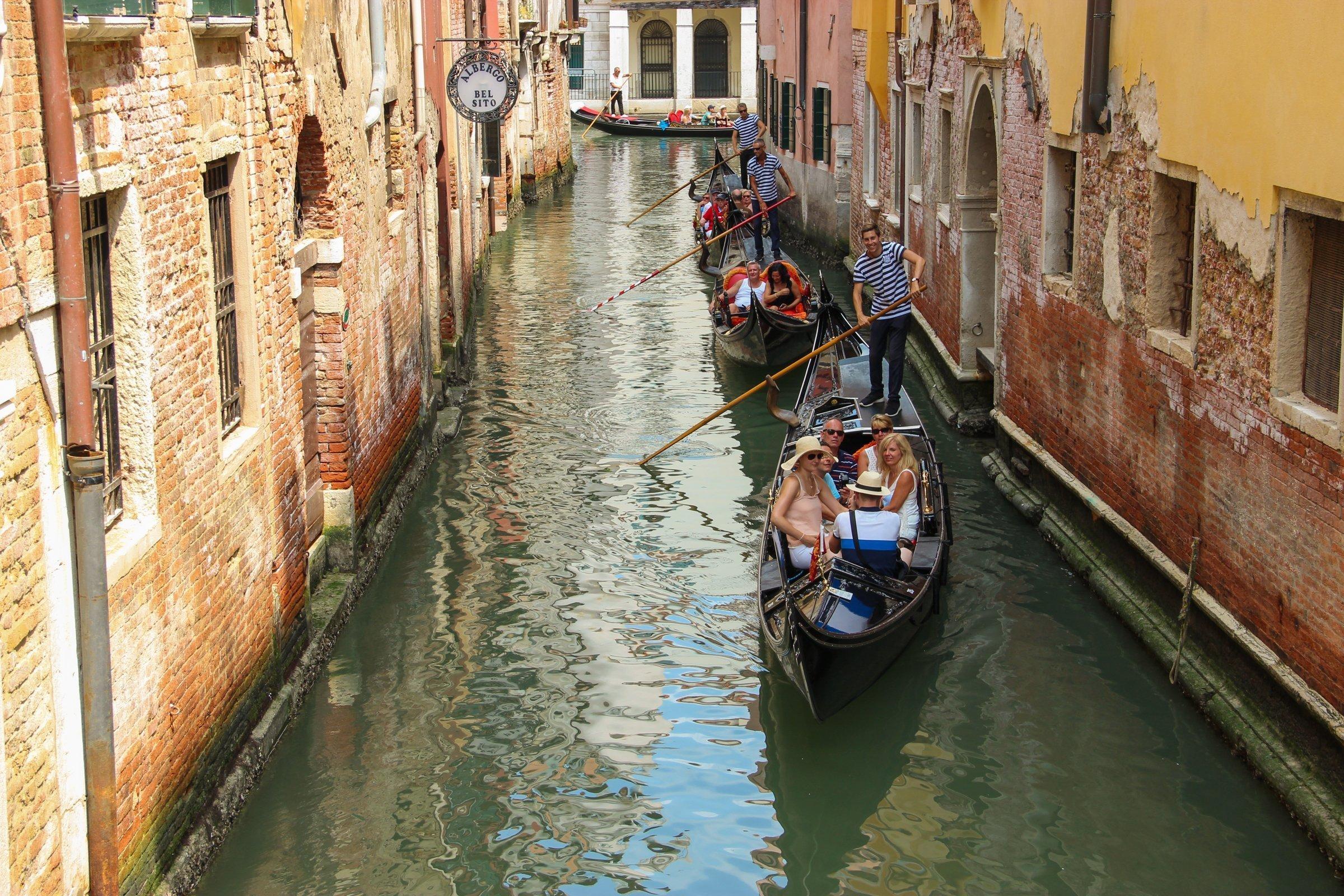 Tourists On Gondolas In Street Between Buildings