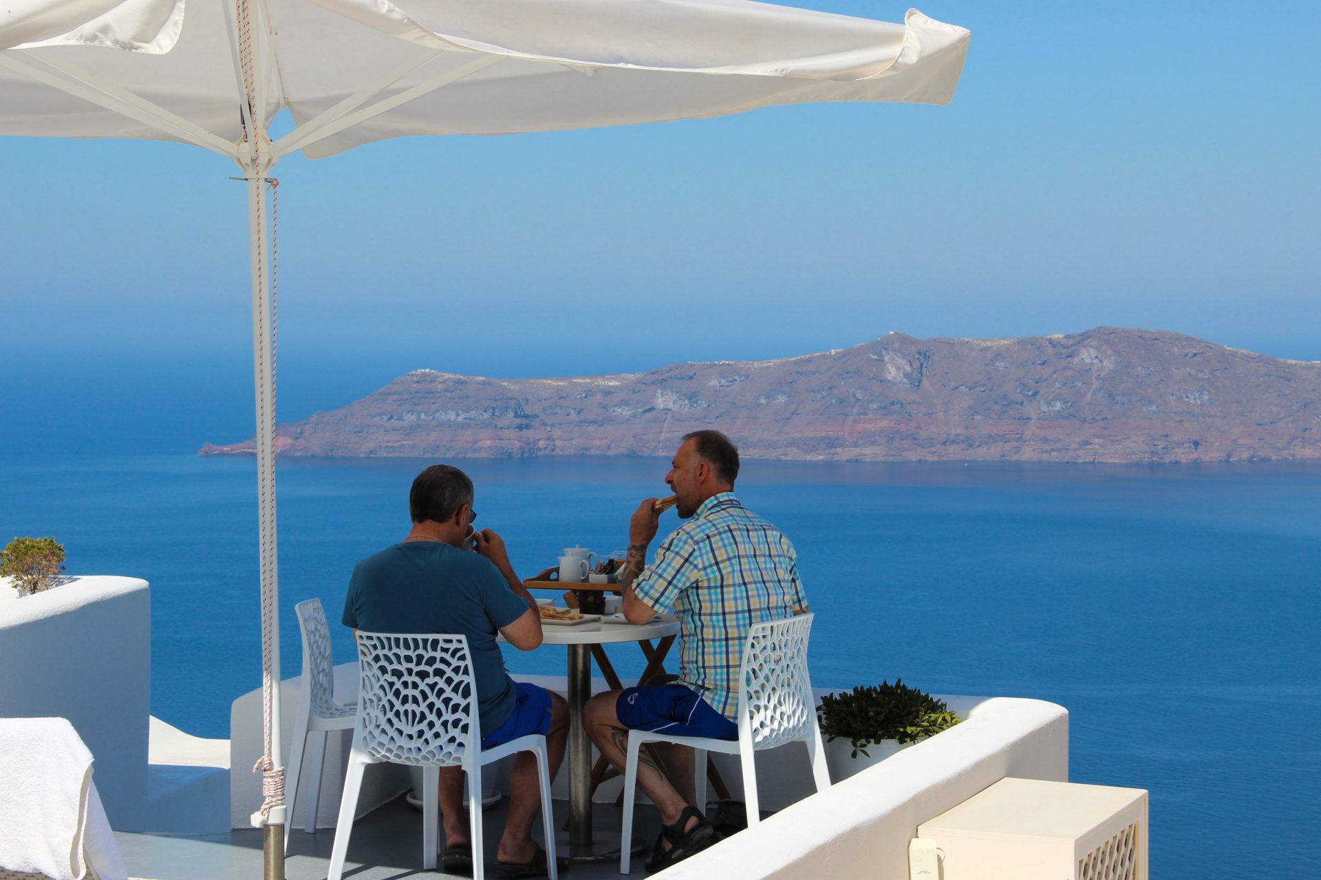 Two Men Eating With Sea View
