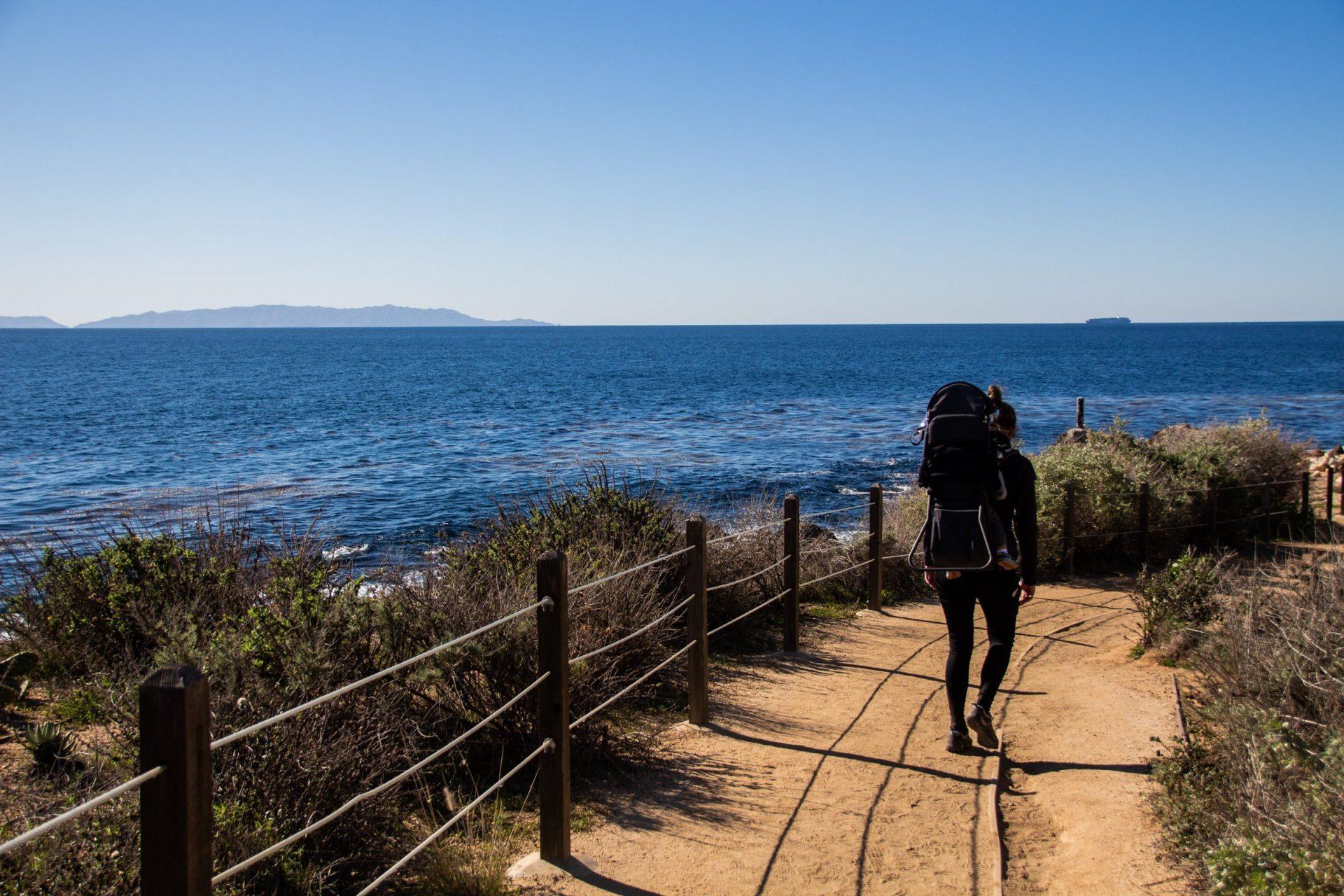 Hiker Walking On Sandy Trail Near Water