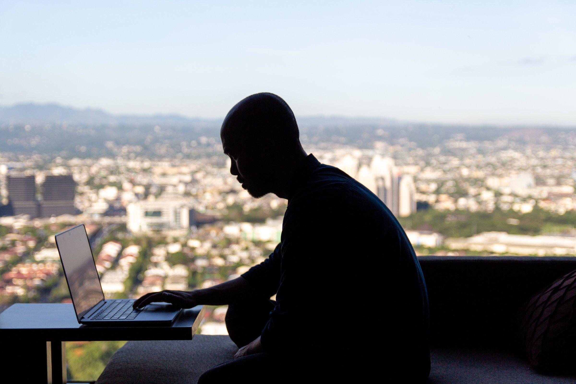 Man On Laptop Near Window