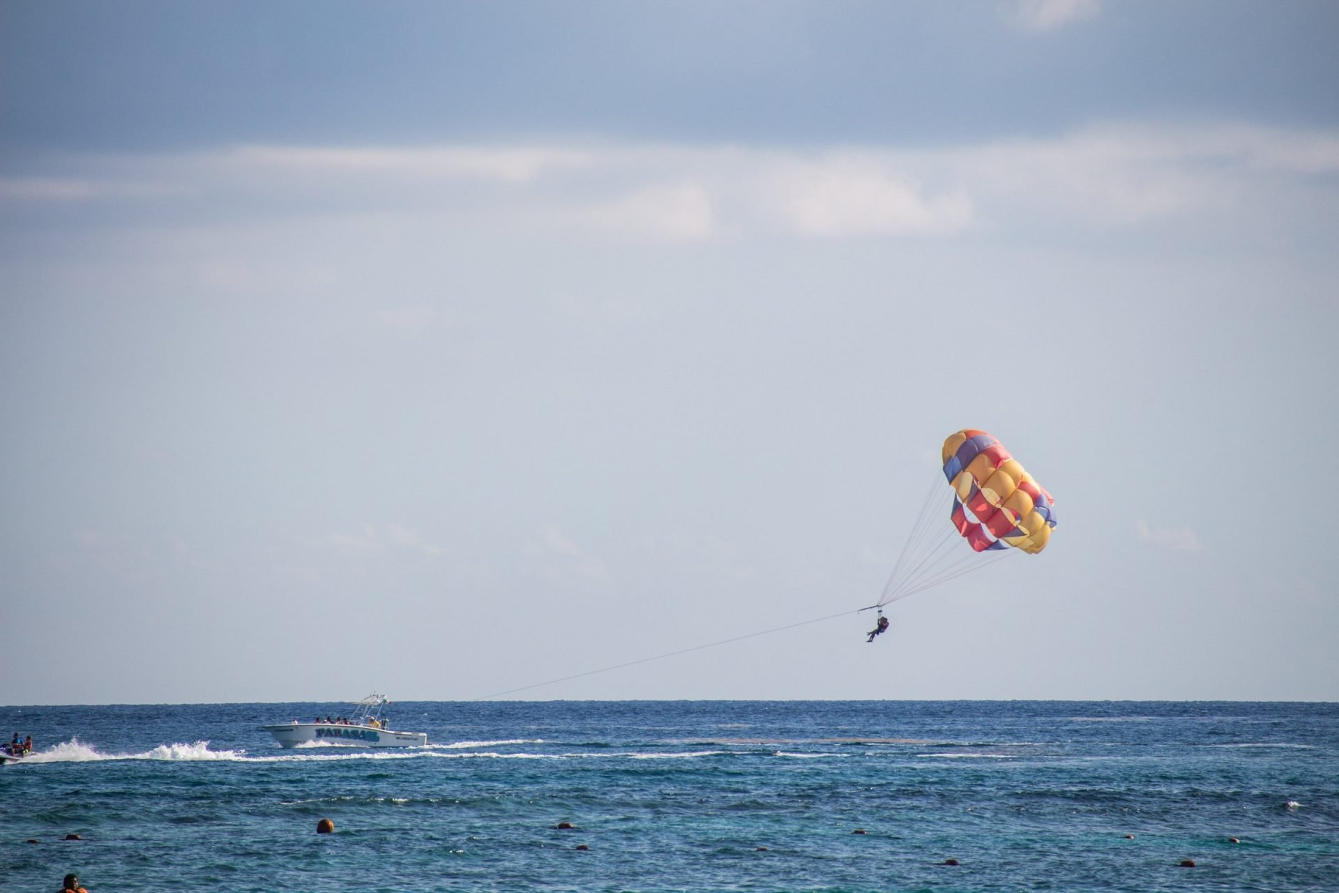 Person Parasailing With Boat Over Water