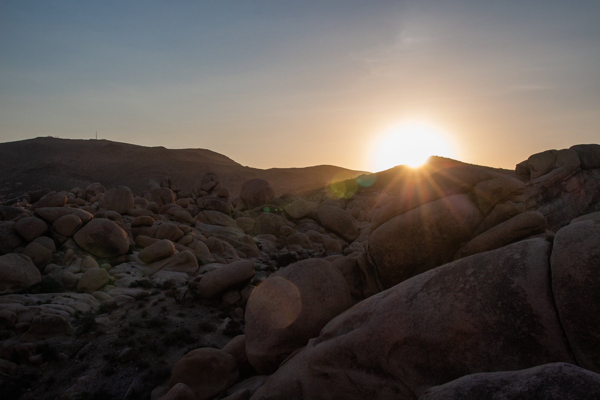 Sunset Over Hills And Boulders