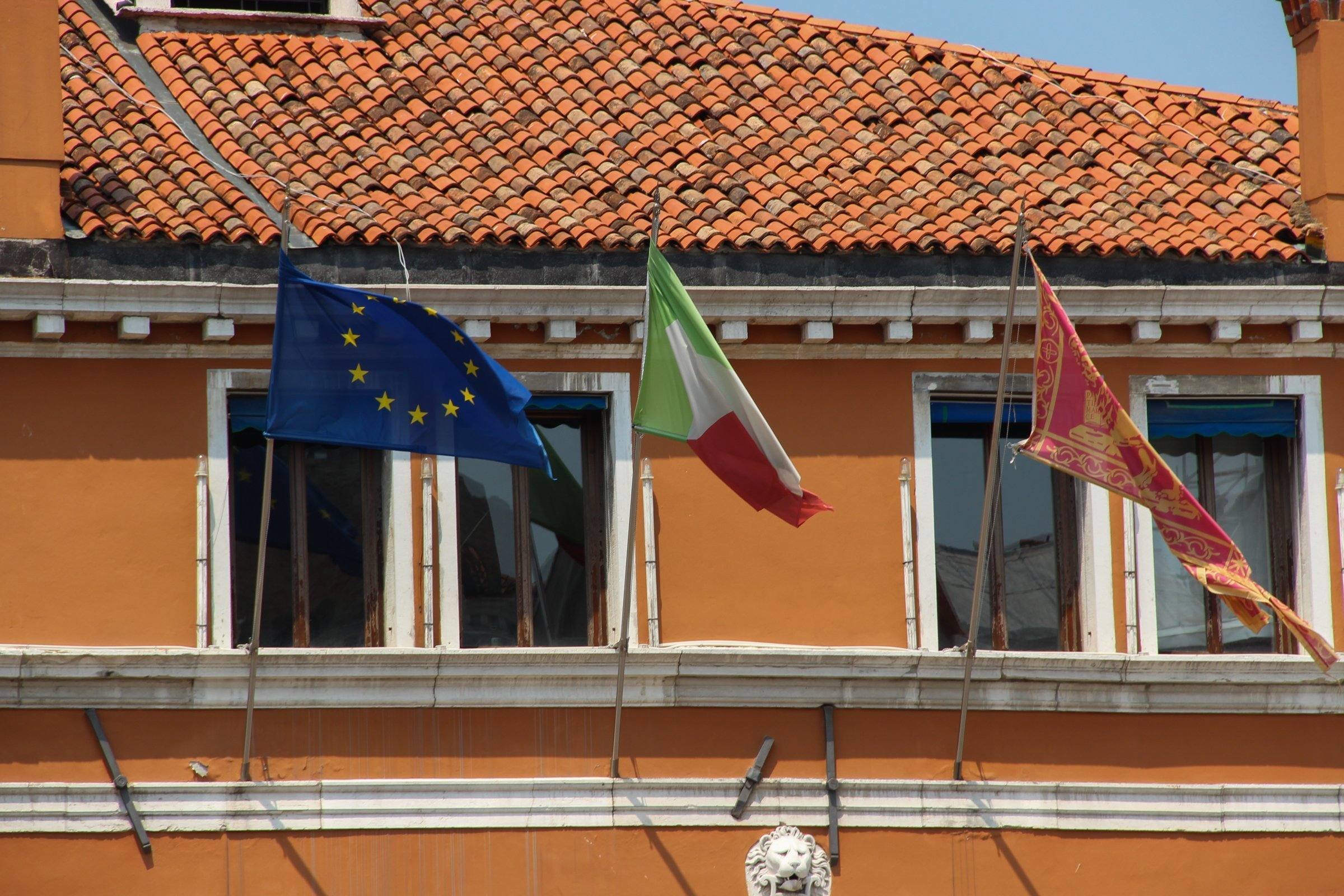 Three Flags On Ocher Colored Building