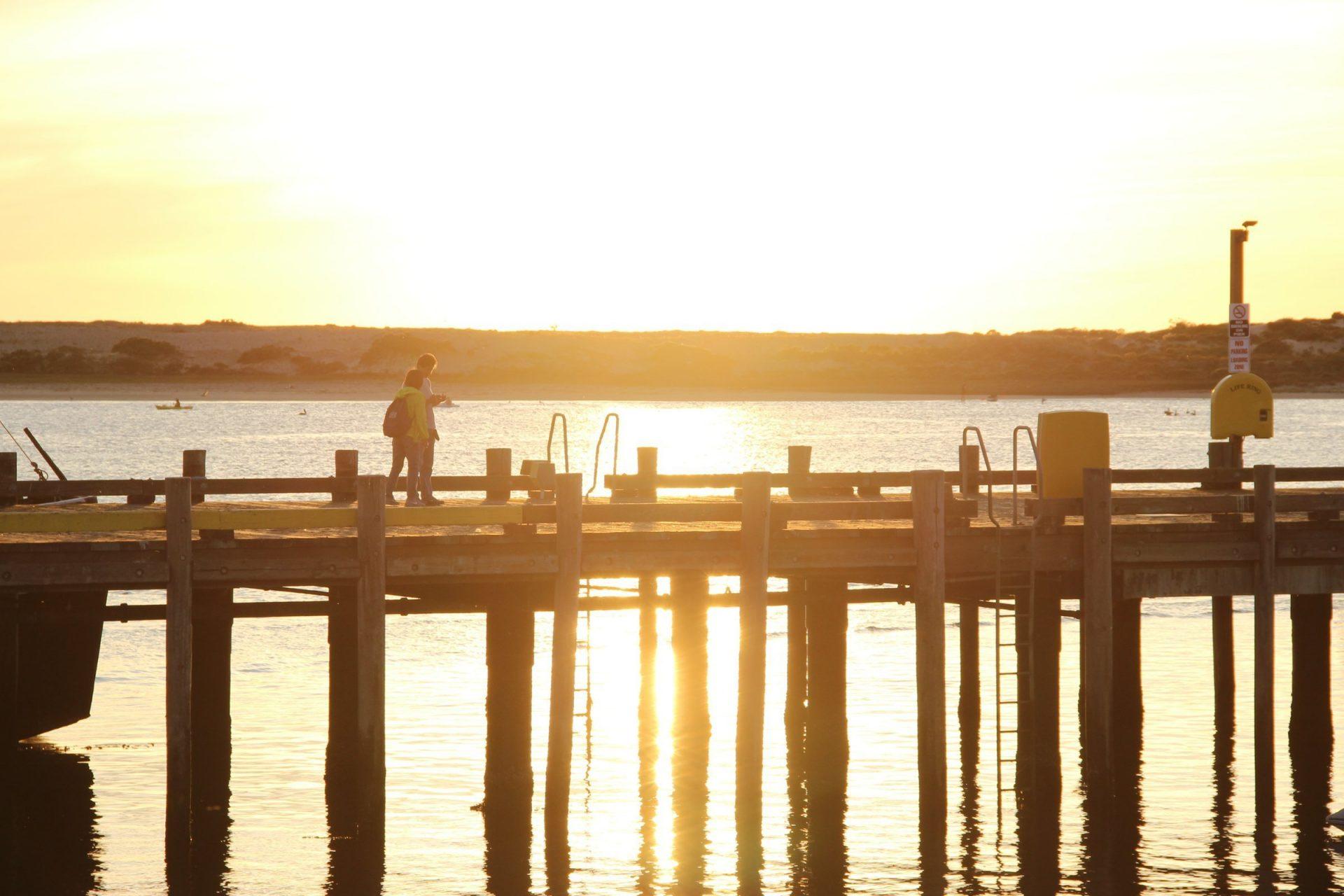 Two People Walking On Pier During Sunset
