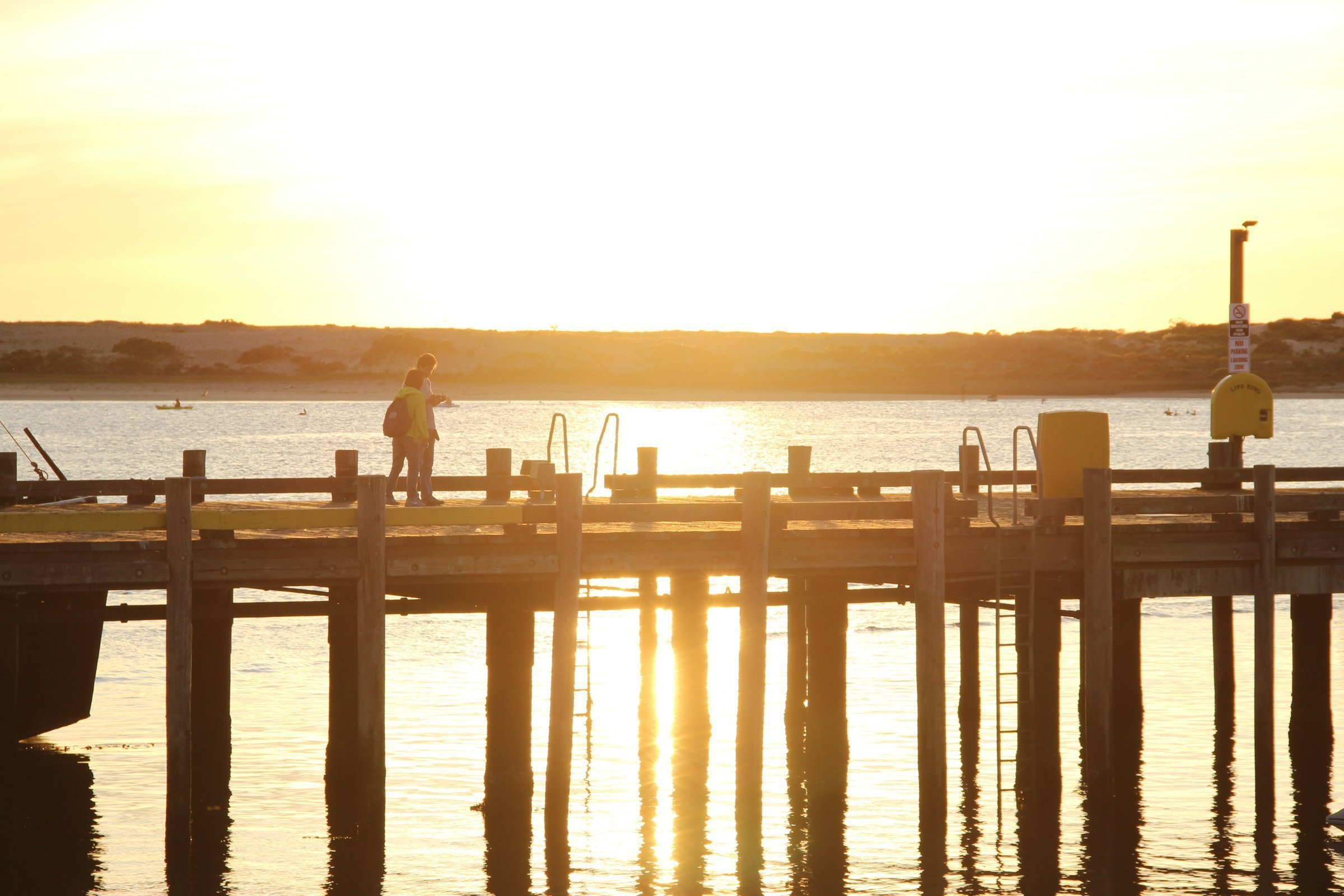 Two People Walking On Pier During Sunset