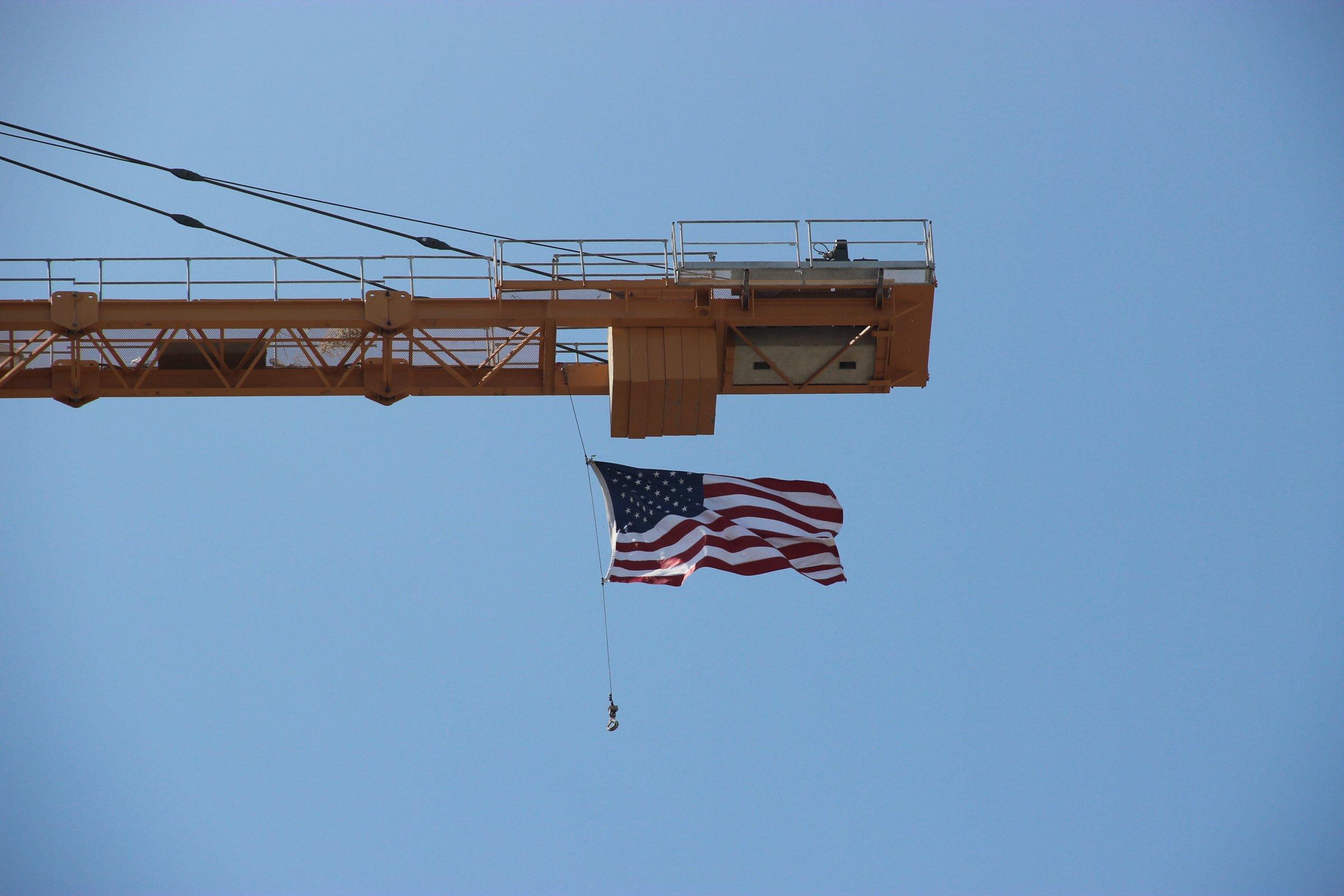 American Flag Swinging From Crane