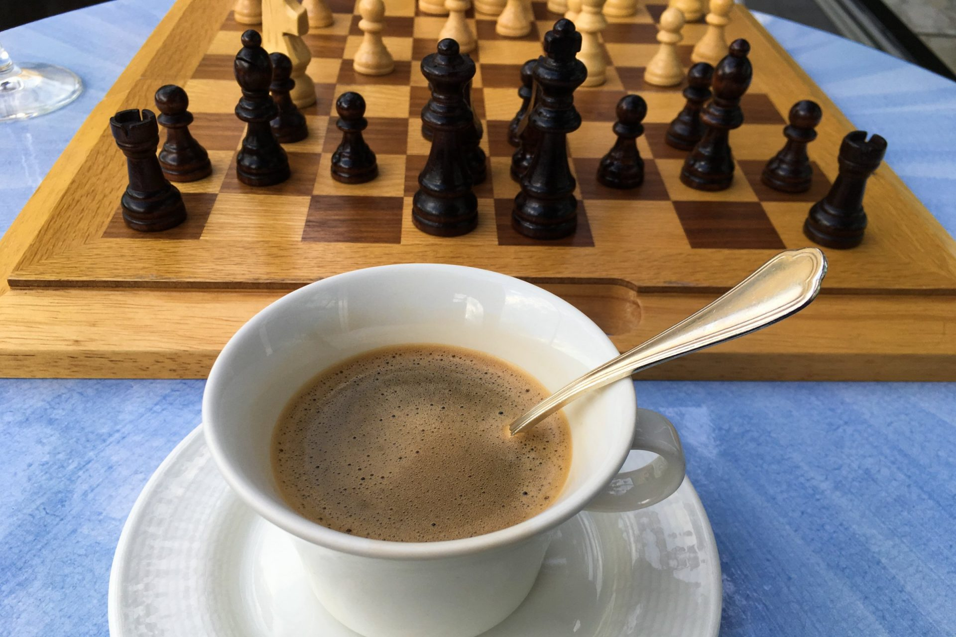 Cup Of Coffee Next To Chessboard On Table