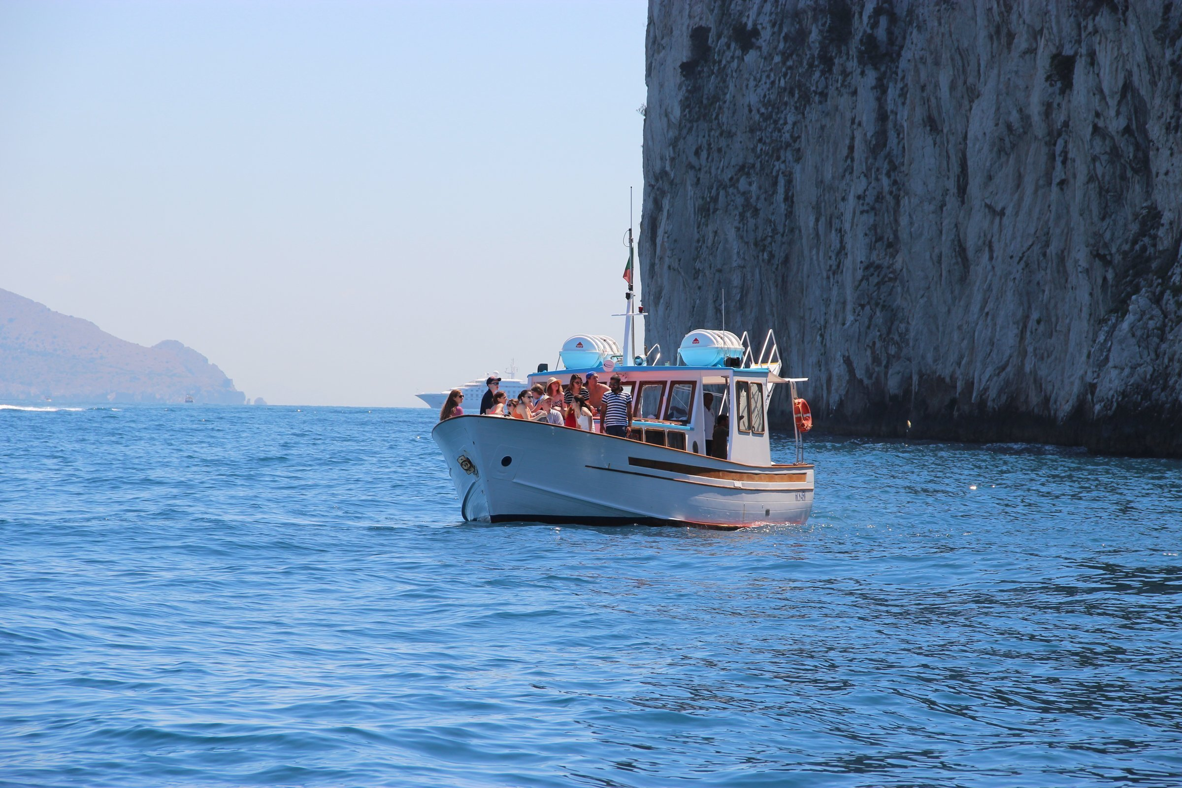 People On Boat In Water Near Cliff