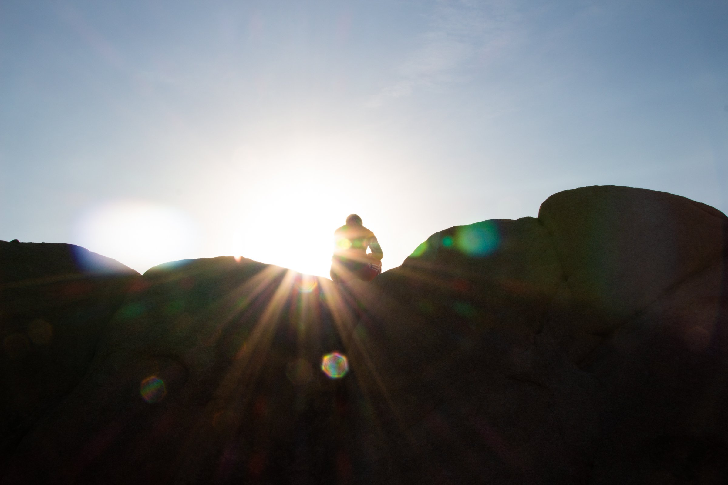 Silhouette Of Person On Rock Against Sunshine