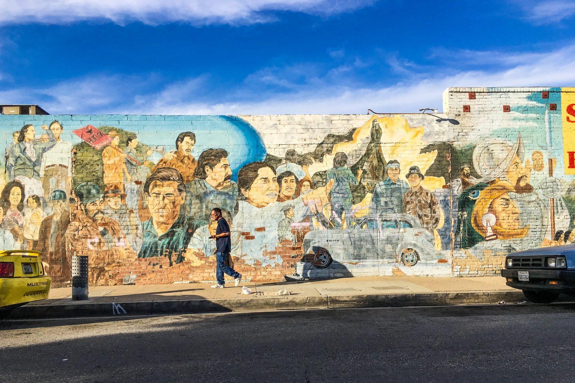 Man Walking Near Street Art Paintings