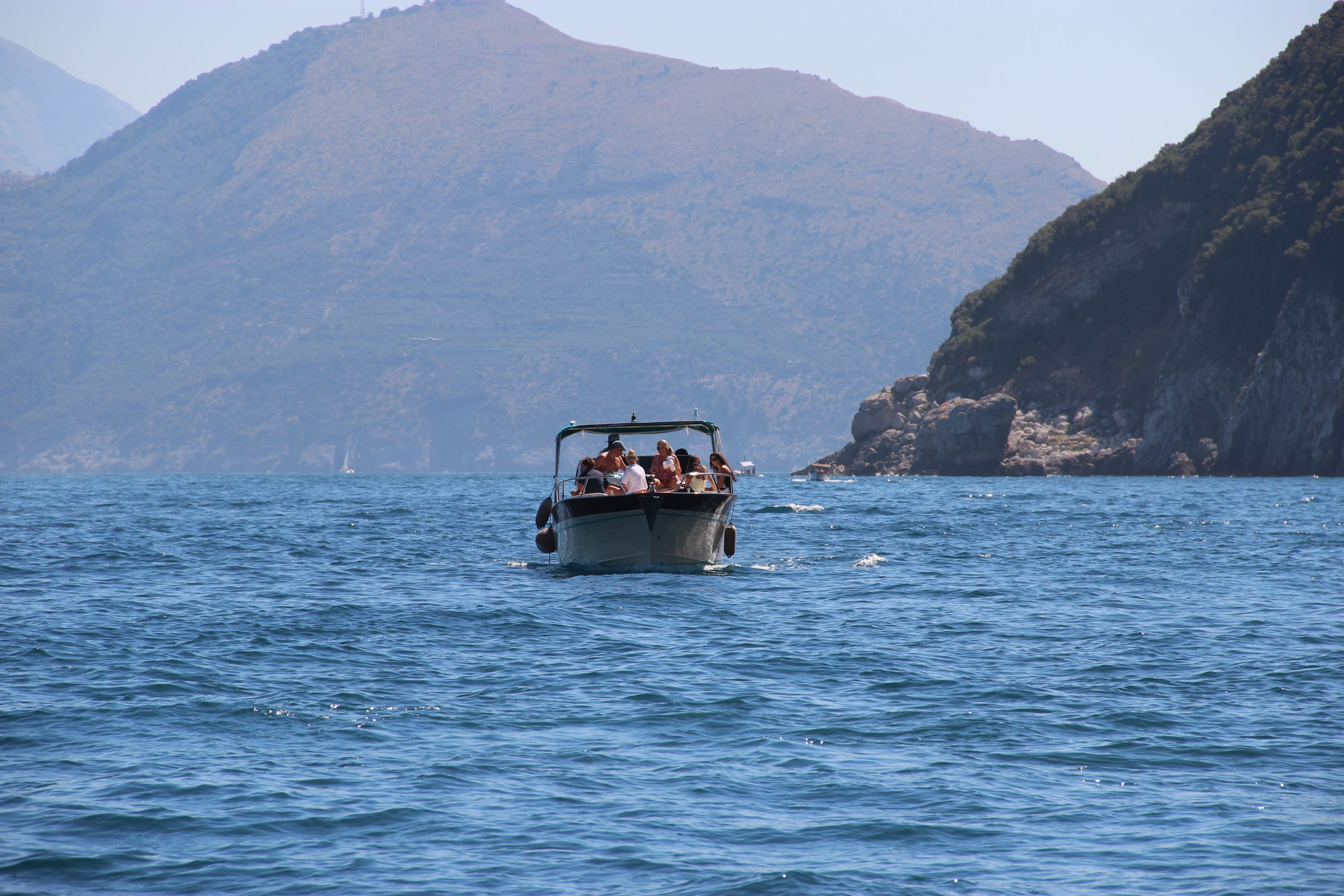 People On Boat In Water Near Mountains