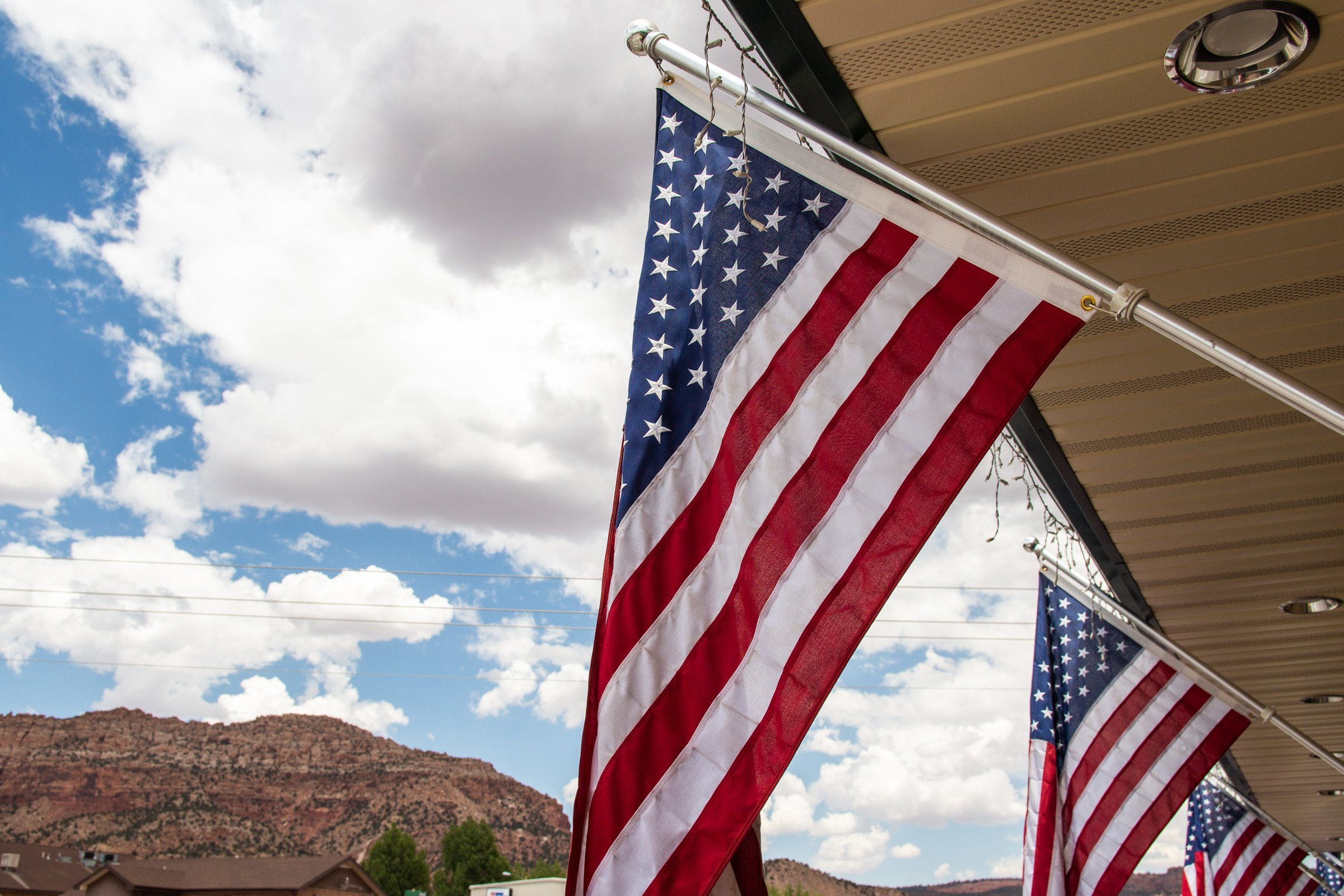 American Flags Under Portico Near Mountains