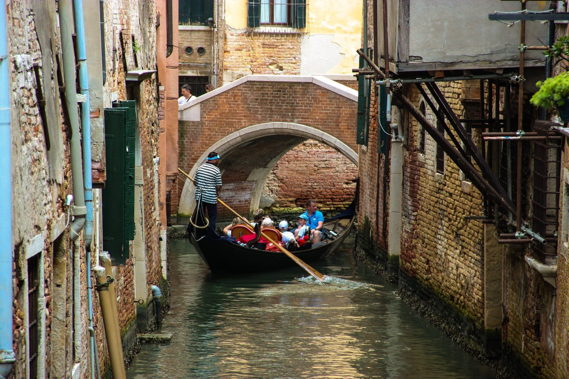 Tourists On Gondola In Canal Near Bridge