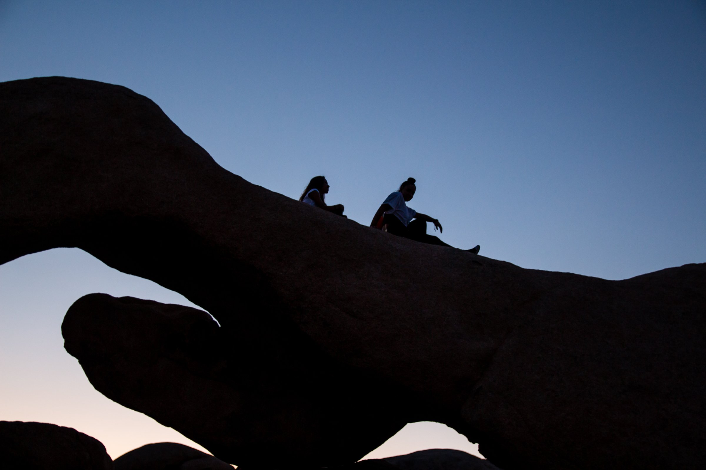 Two Women On Top Of Rock Formation