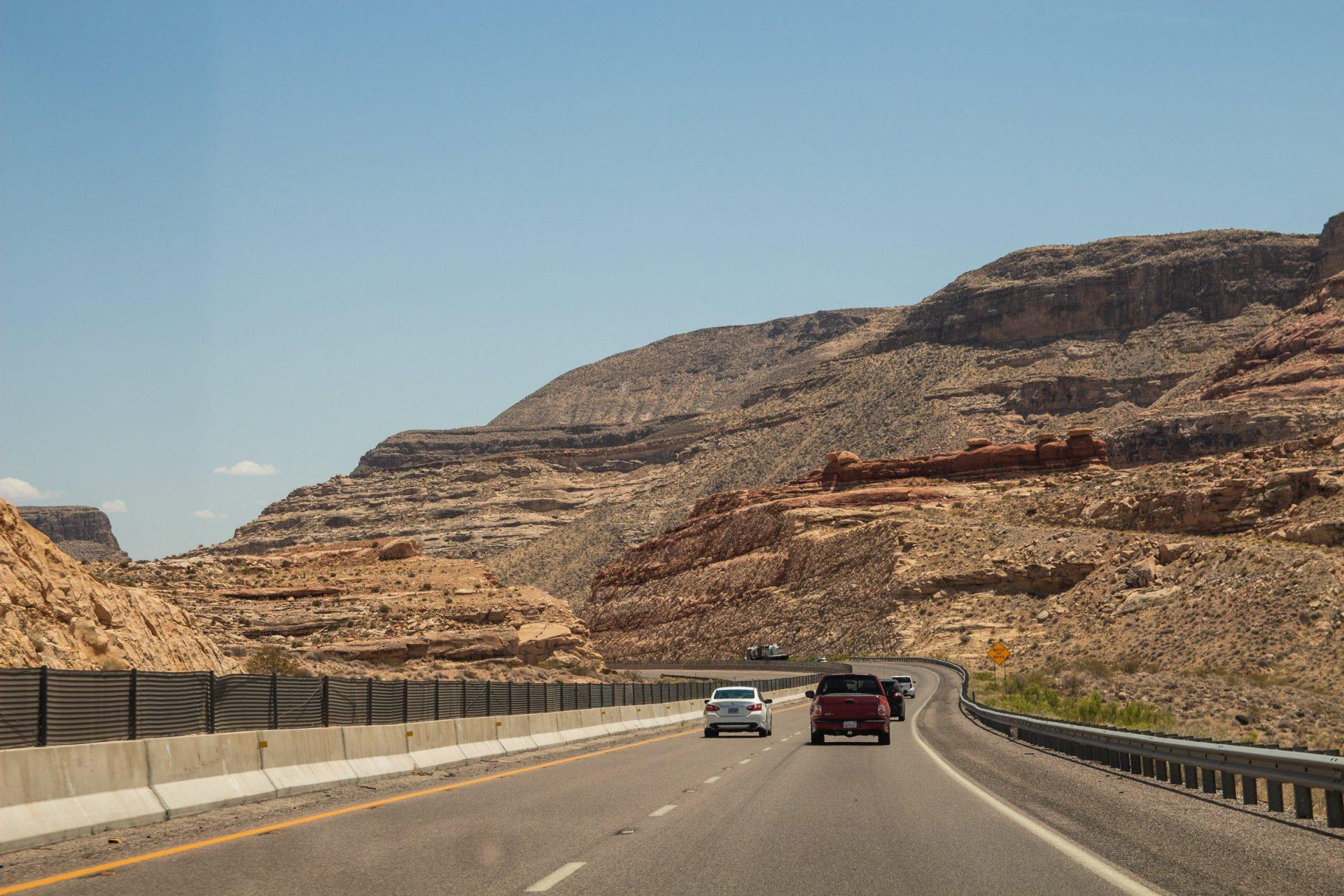Vehicles In Highway Between Mountains