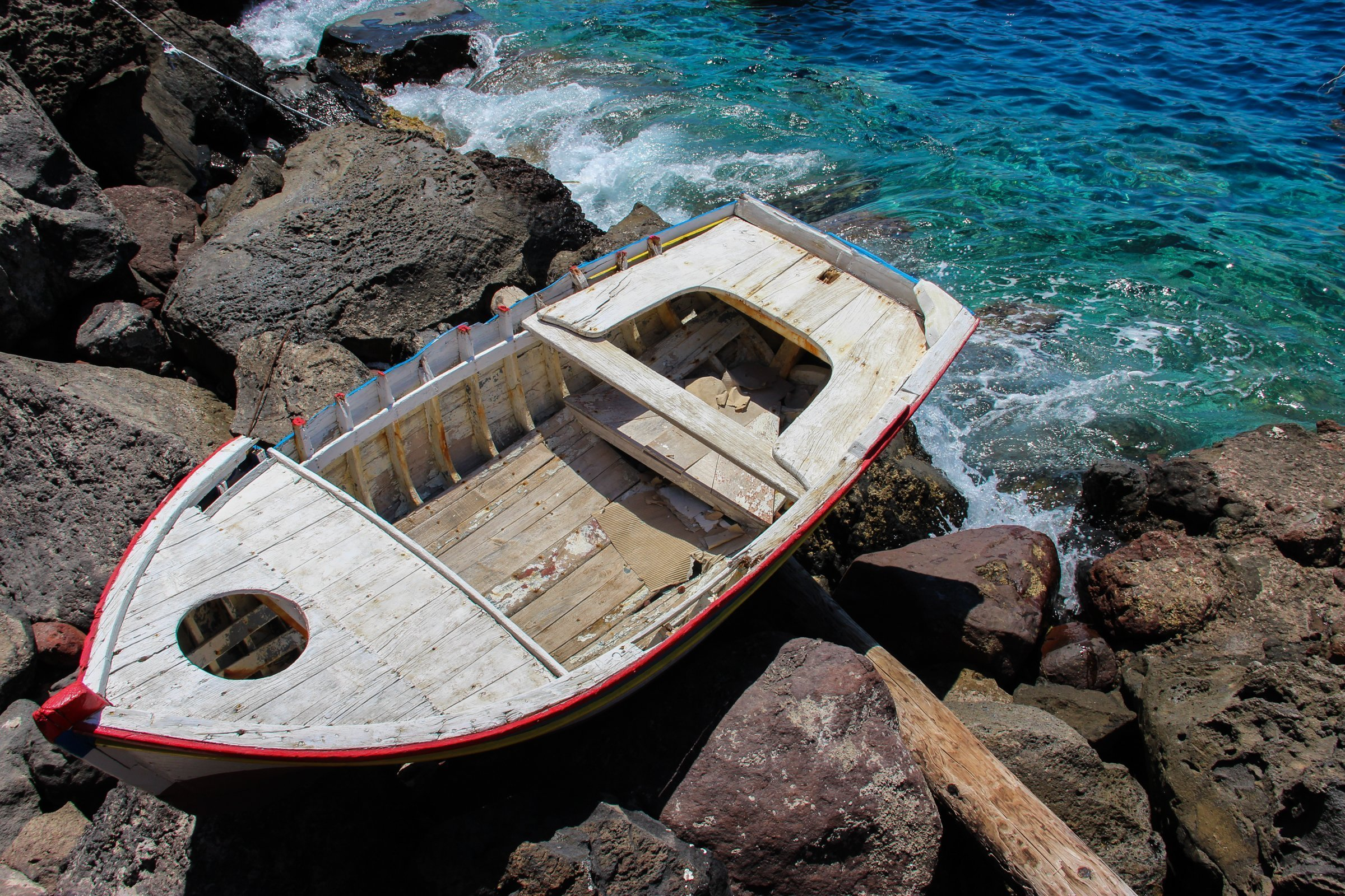 Old Wooden Boat On Rocks Near Water