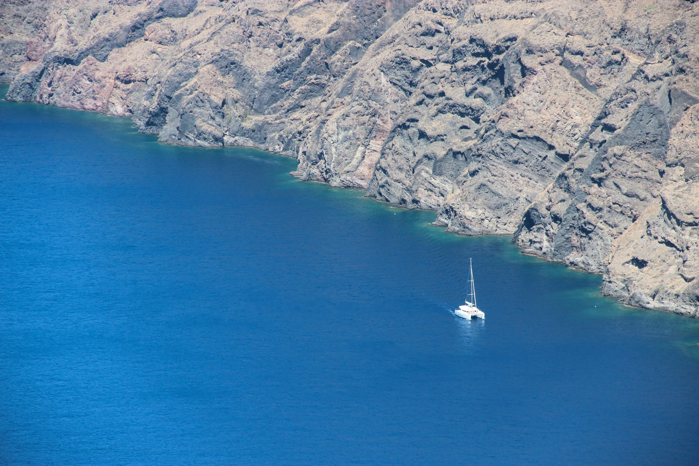 Sailing Yacht Near Rocky Cliff Shore