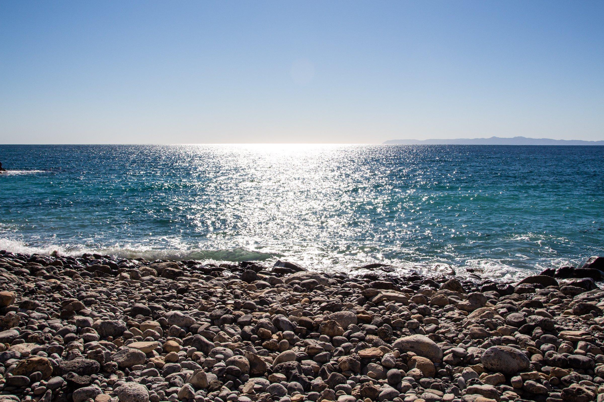 Sunlight On Water Near Rocky Beach
