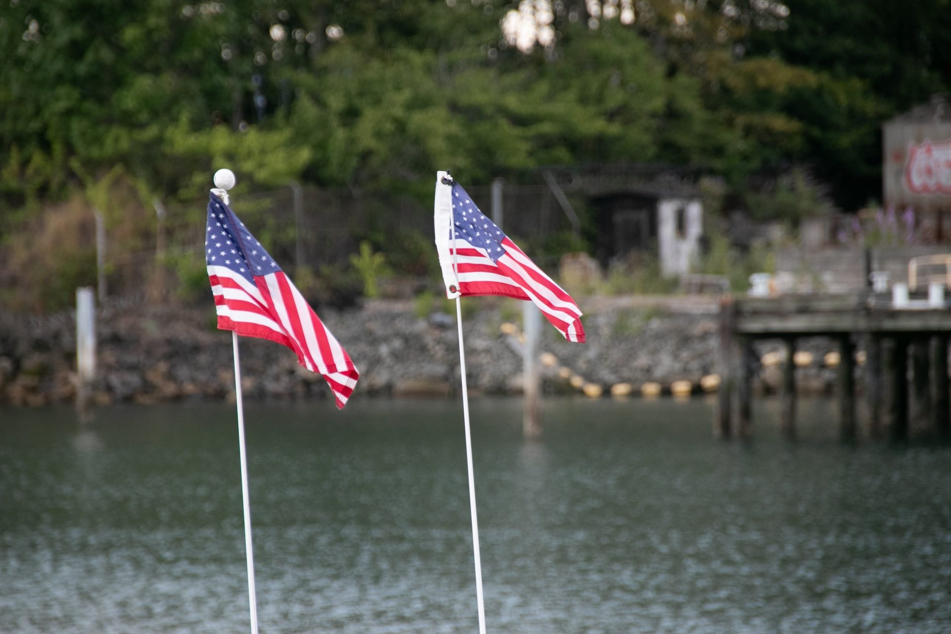 Two Small American Flags Near Water