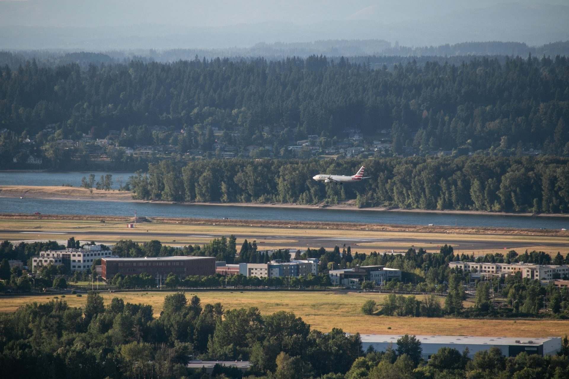 Commercial Plane Preparing To Land Near River And Forest