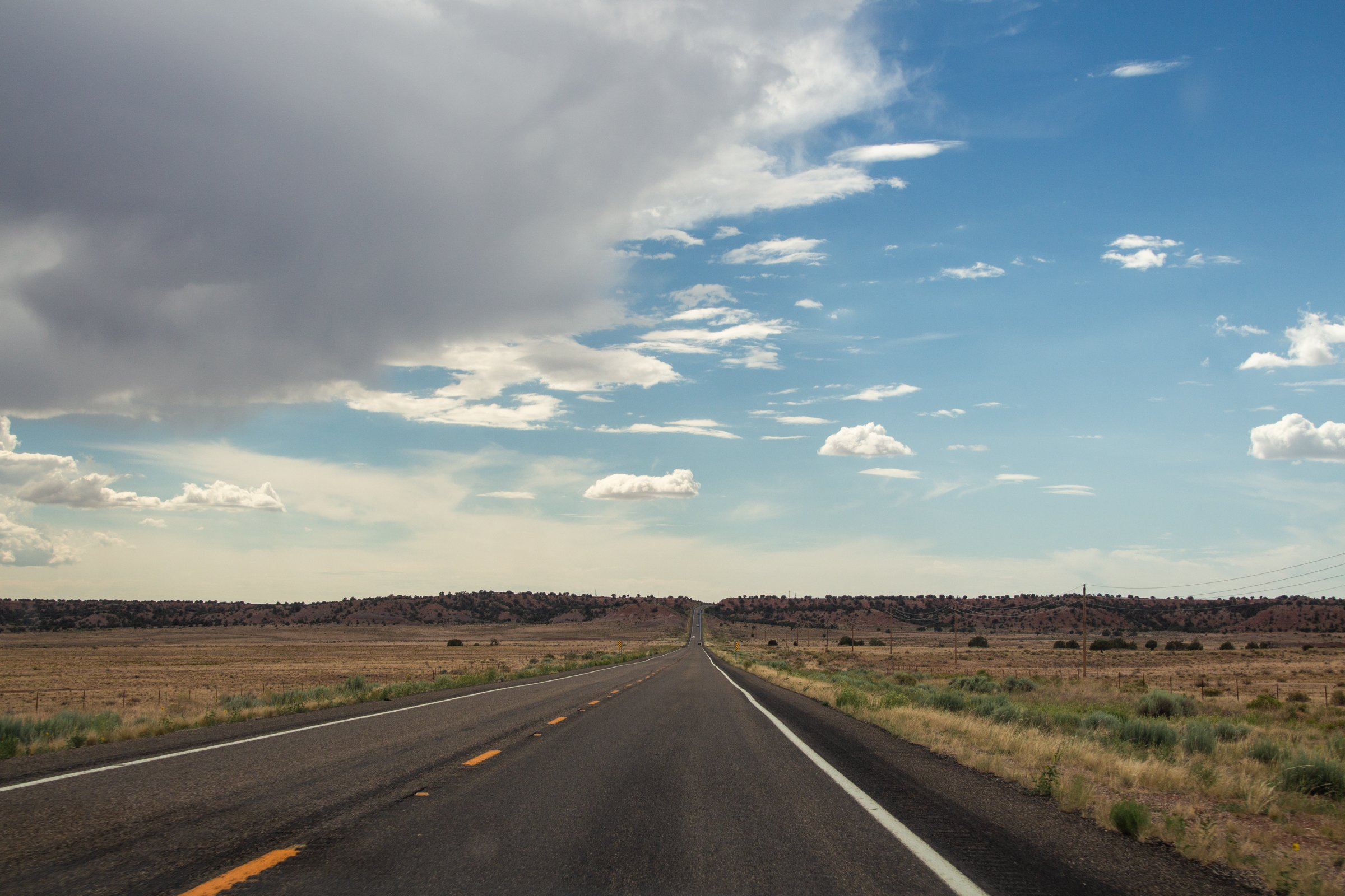 Empty Highway In Desert Under Cloudy Blue Sky