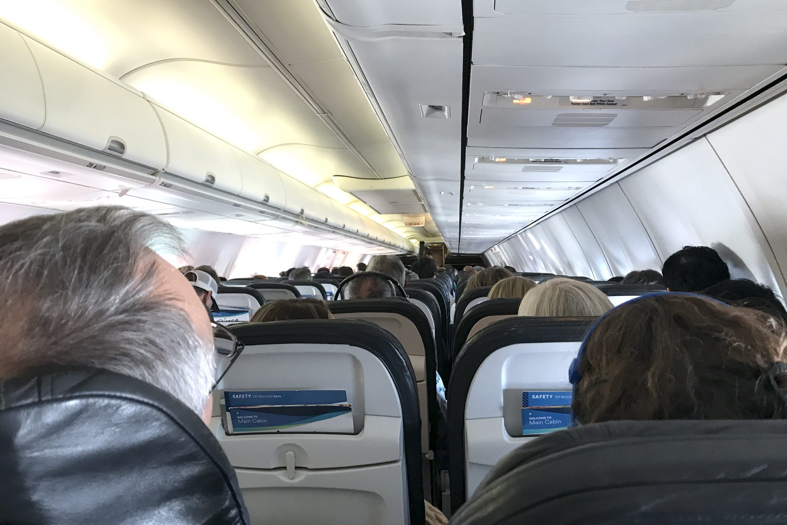 Rows Of Passengers Sitting On Plane
