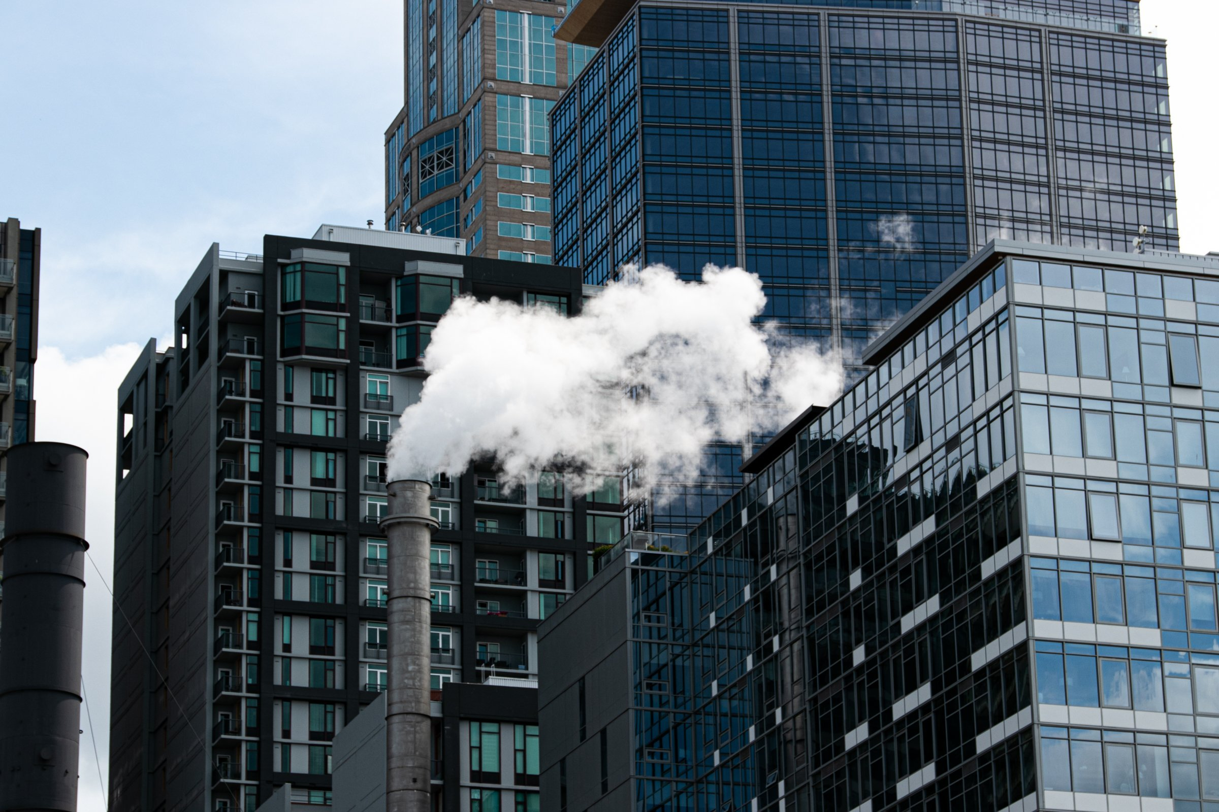 White Smoke From Chimney Surrounded By Tall Buildings