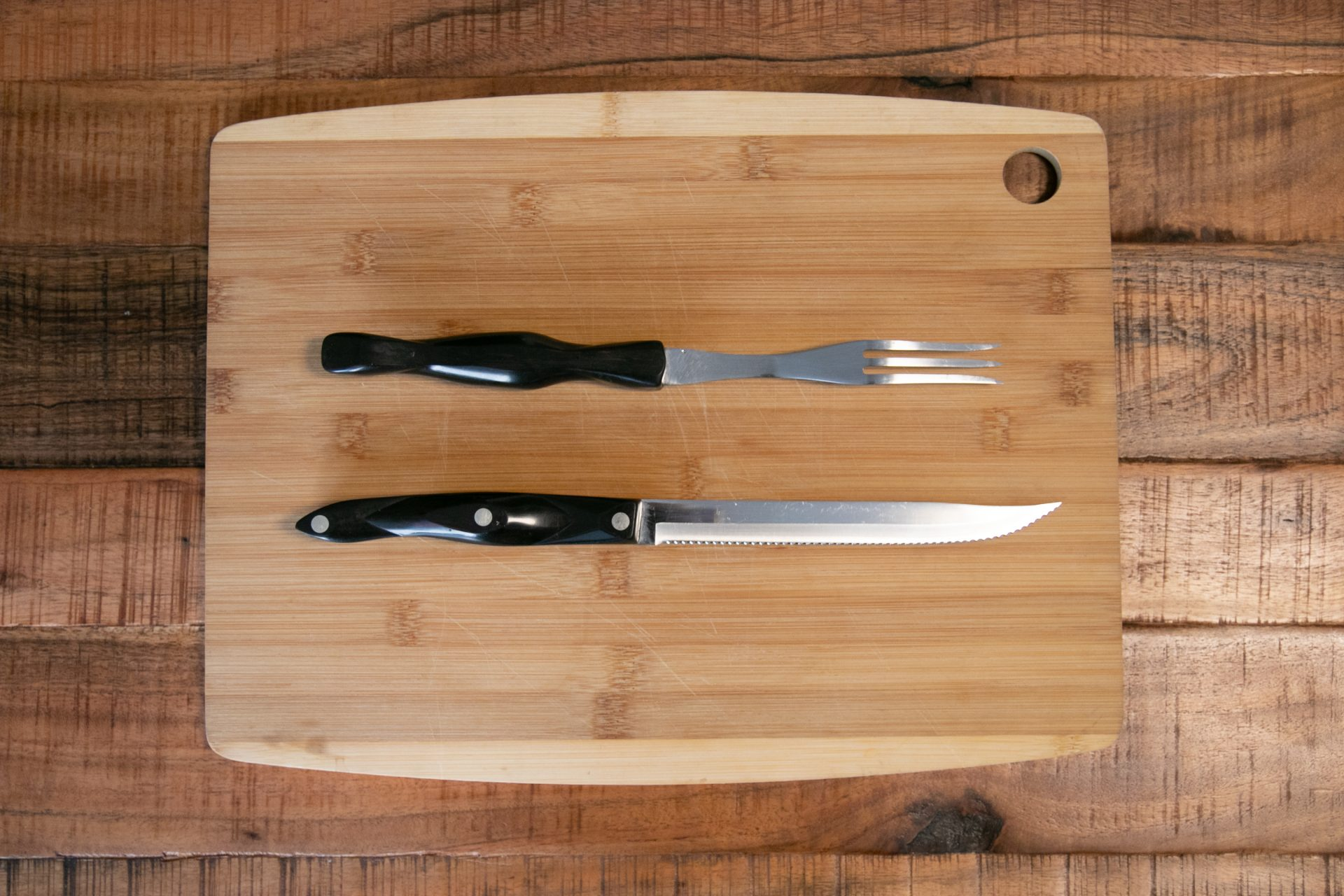 Fork And Knife On Wooden Cutting Board